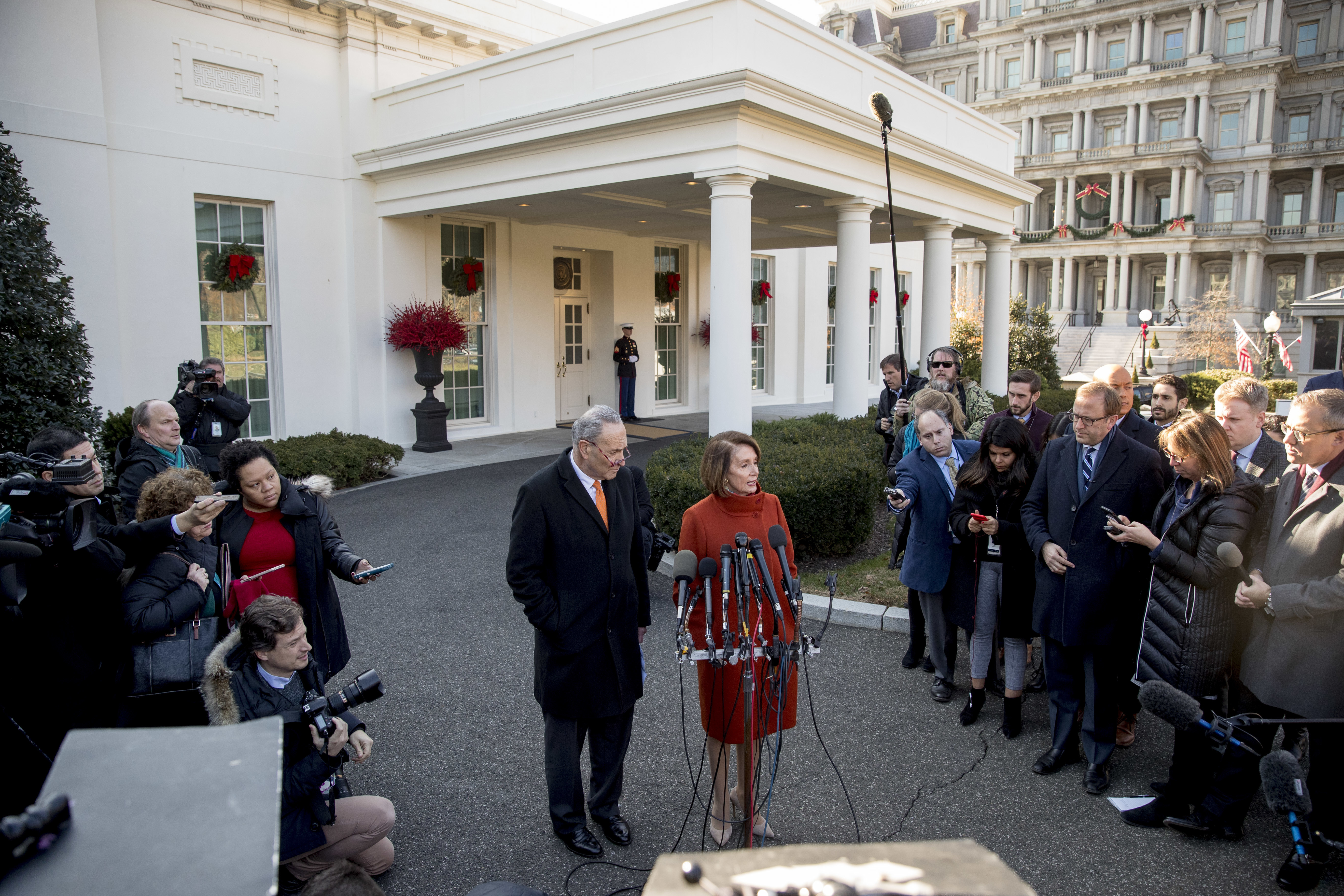 House Minority Leader Nancy Pelosi of Calif., right, accompanied by Senate Minority Leader Sen. Chuck Schumer of N.Y., left, speaks to members of the media outside the West Wing of the White House in Washington, Tuesday, Dec. 11, 2018, following a me...