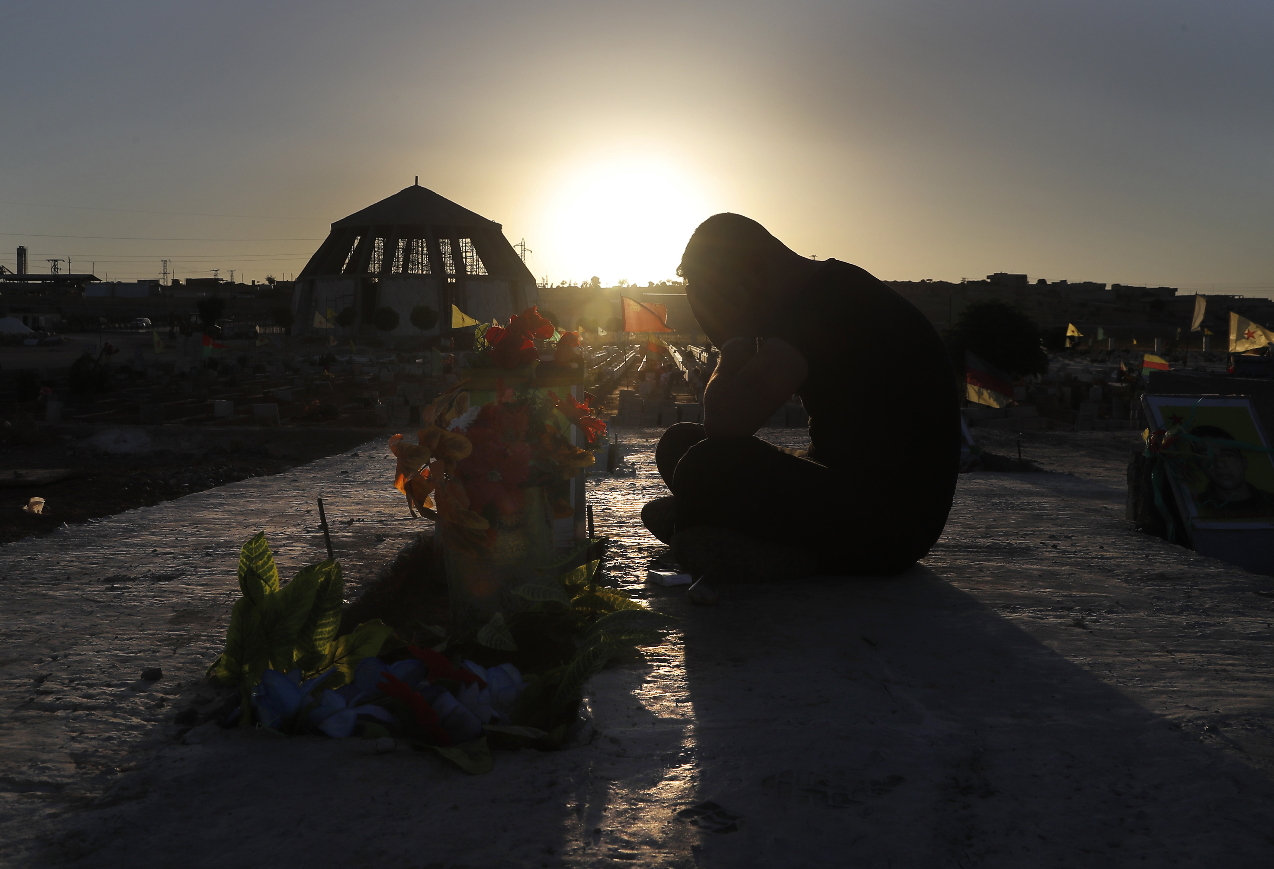 a Kurdish man mourns as he sits next to the grave of his friend who was killed while fighting against Islamic State militants in Raqqa, at a cemetery in Kobani, Syria, July 28, 2017.