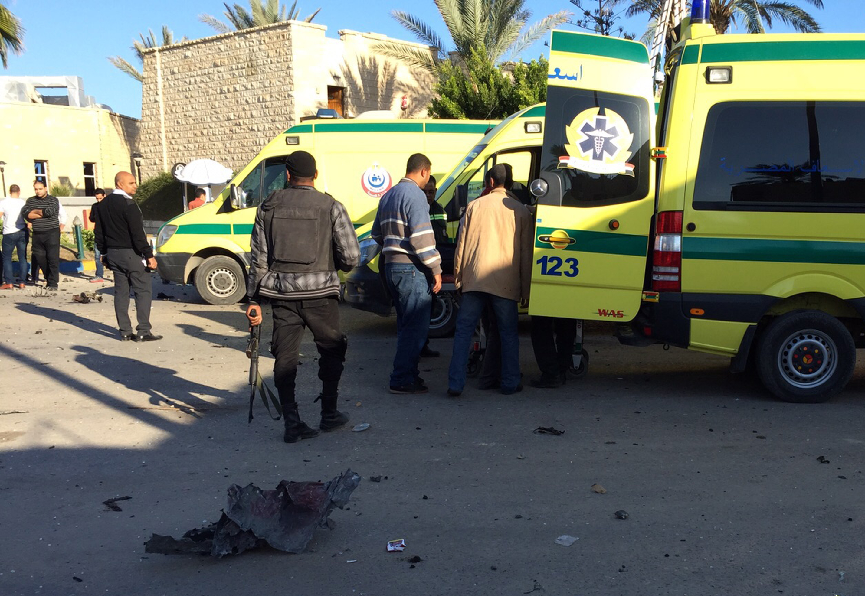 Emergency personnel and security forces stand next to ambulances outside the Swiss Inn hotel in the Egyptian town of El-Arish, in the Sinai peninsula, following an attack on the hotel Nov. 24, 2015.