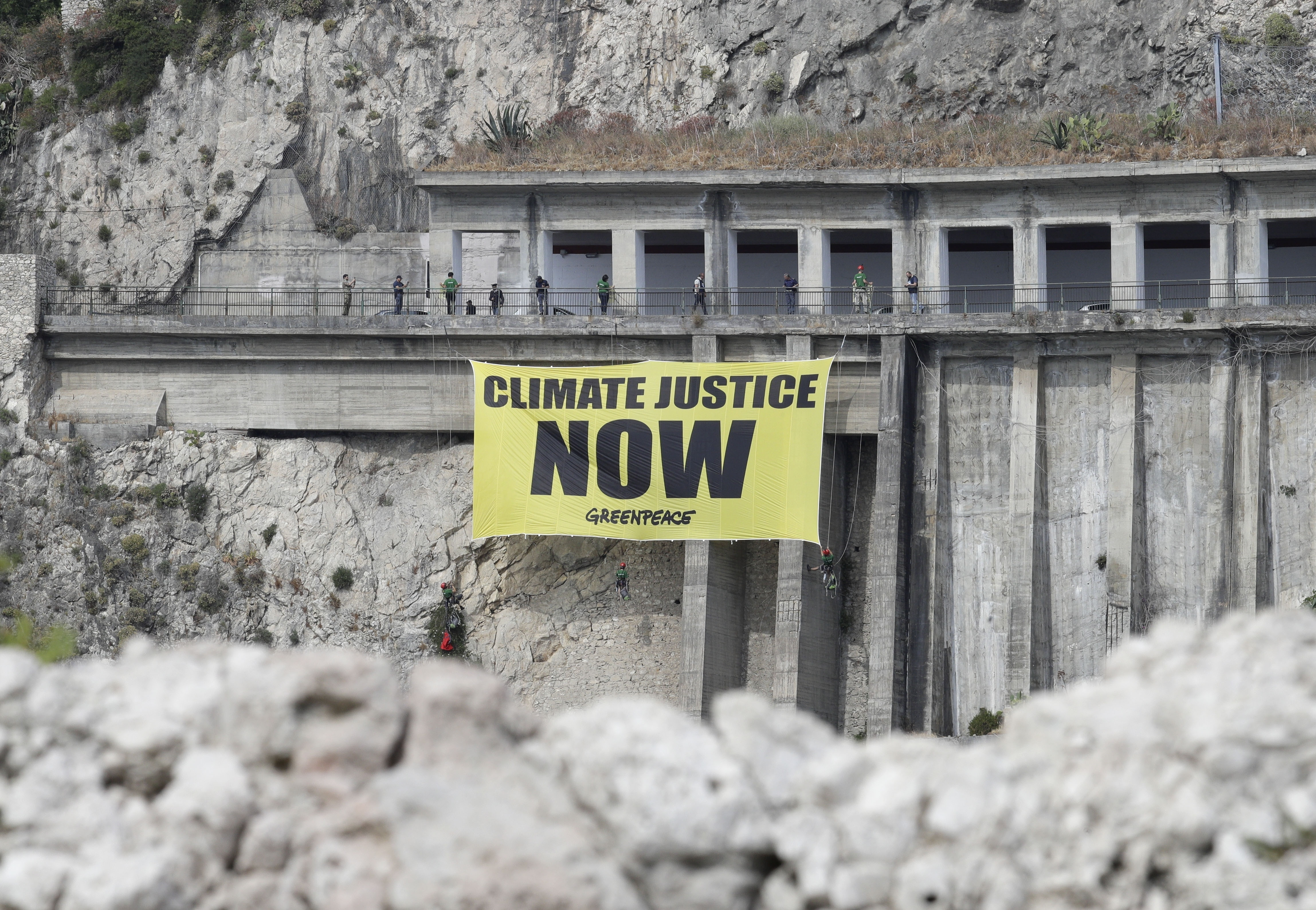 Greenpeace activists hang a banner on climate issues along a road above the beach of Isolabella, ahead of a G-7 summit scheduled for May 26 and 27, in the Sicilian town of Taormina, May 25, 2017.