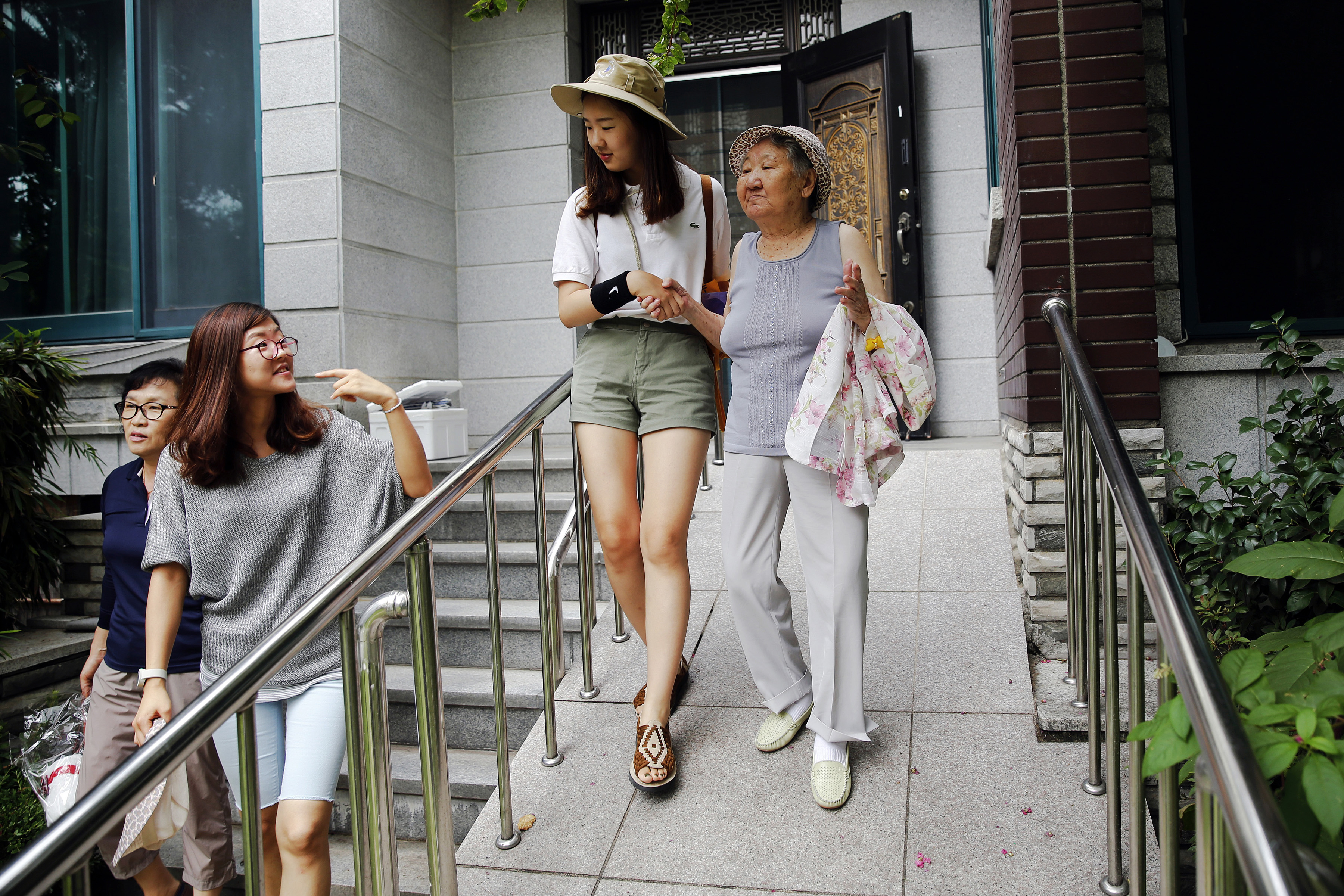 "A volunteer helps South Korean former ""comfort woman"" Gil Won-ok go to a weekly Wednesday protest demanding an apology and compensation from the Japanese government in Seoul, July 22, 2015. Gil, born in 1927 in what is now North Korea, says she was t..."