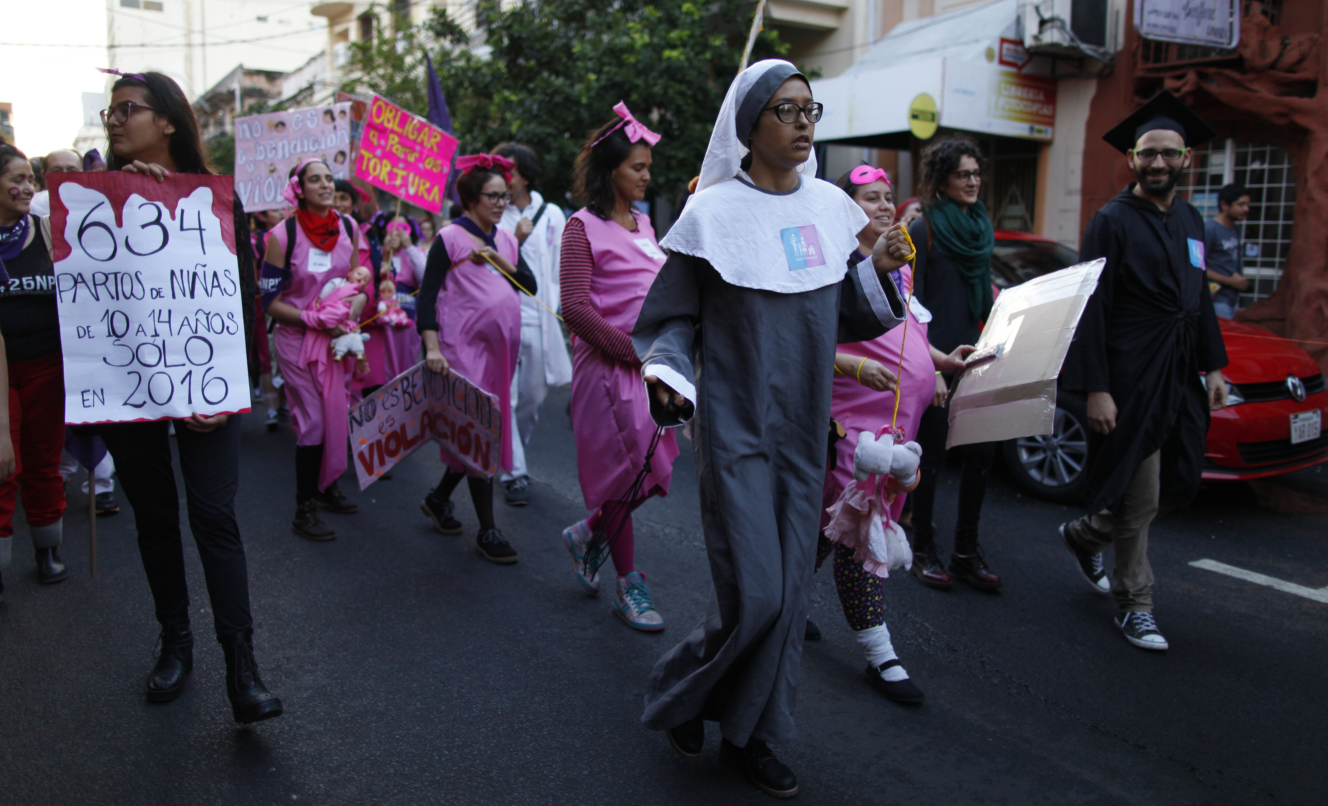 A young woman dressed as a nun leads a group of women depicting pregnant schoolgirls in a march marking the International Day for the Elimination of Violence against Women, in Asuncion, Paraguay, Nov. 25, 2017. According to officials there is at leas...