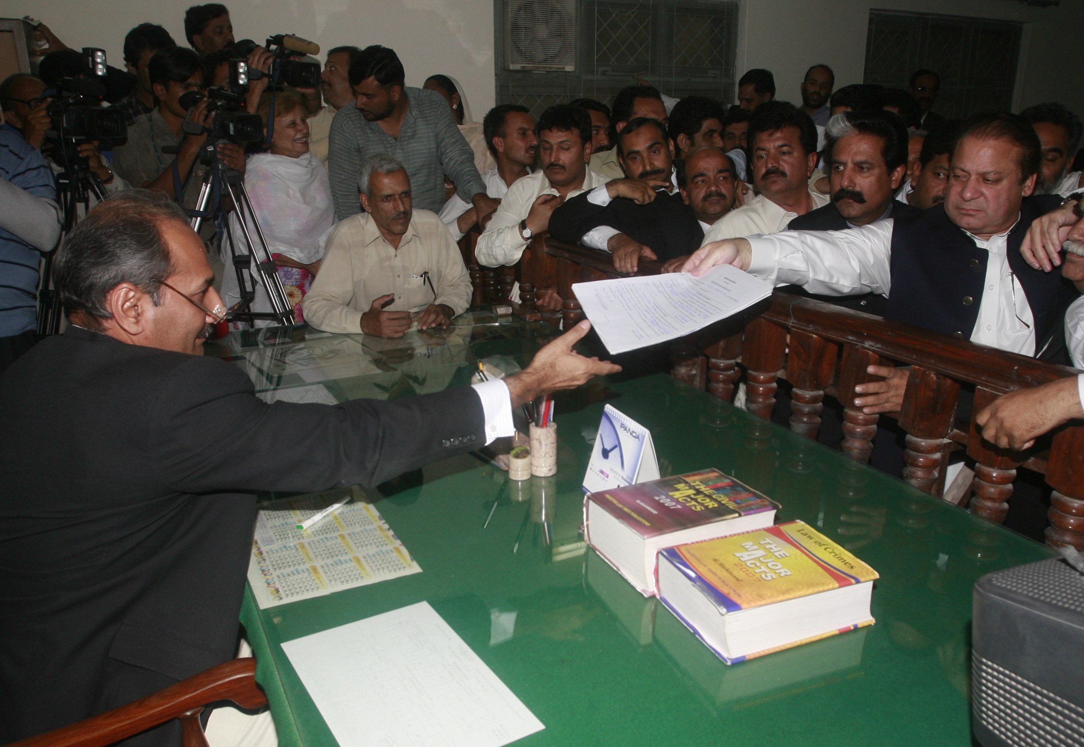 Former prime minister Nawaz Sharif (R) submits his nomination papers to contest a by-election in Rawalpindi May 12, 2008.