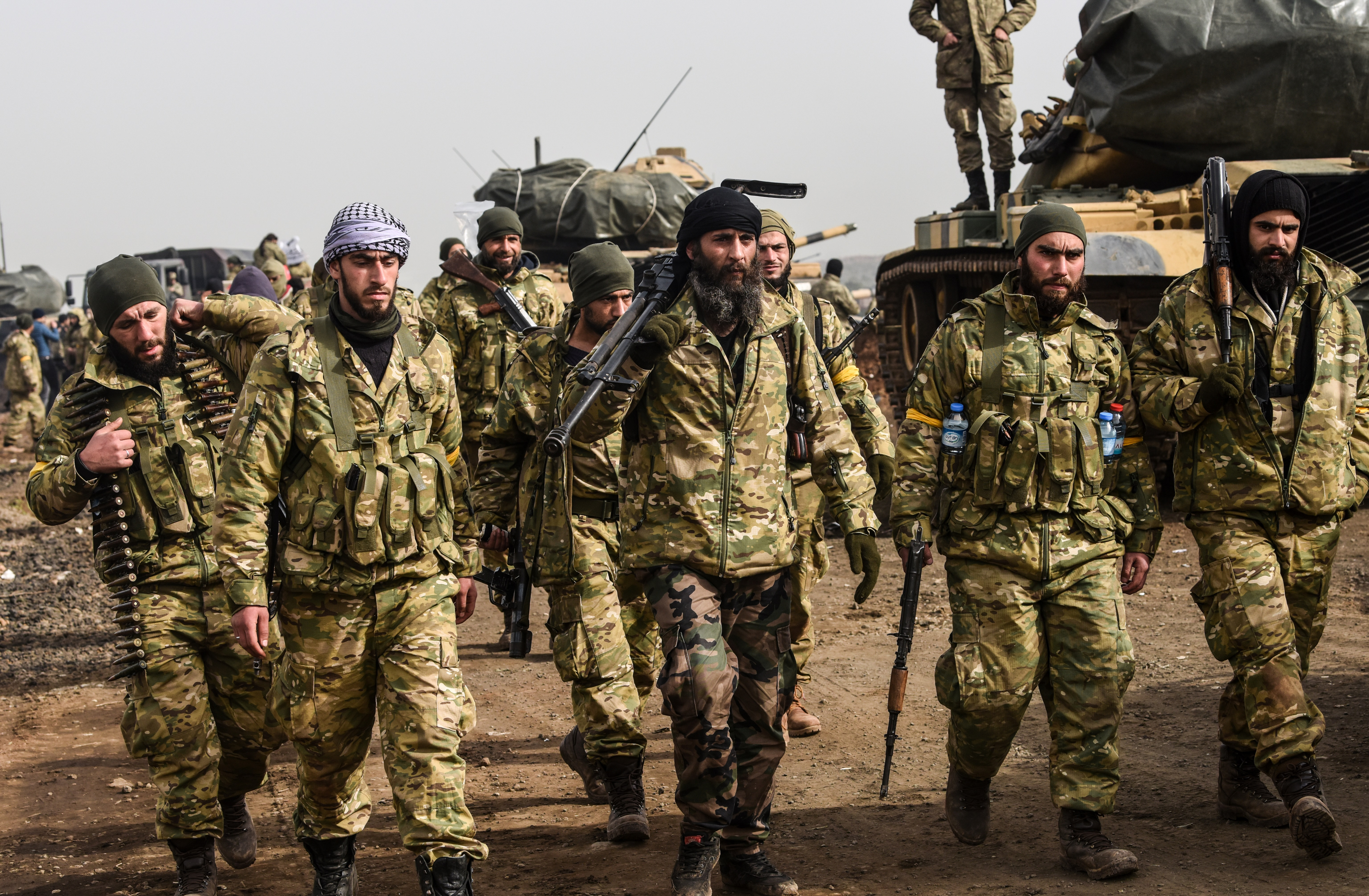Syrian opposition fighters backed by Turkey walk in front of Turkish troops near the Syria border at Hassa, Hatay province on Jan. 22, 2018.