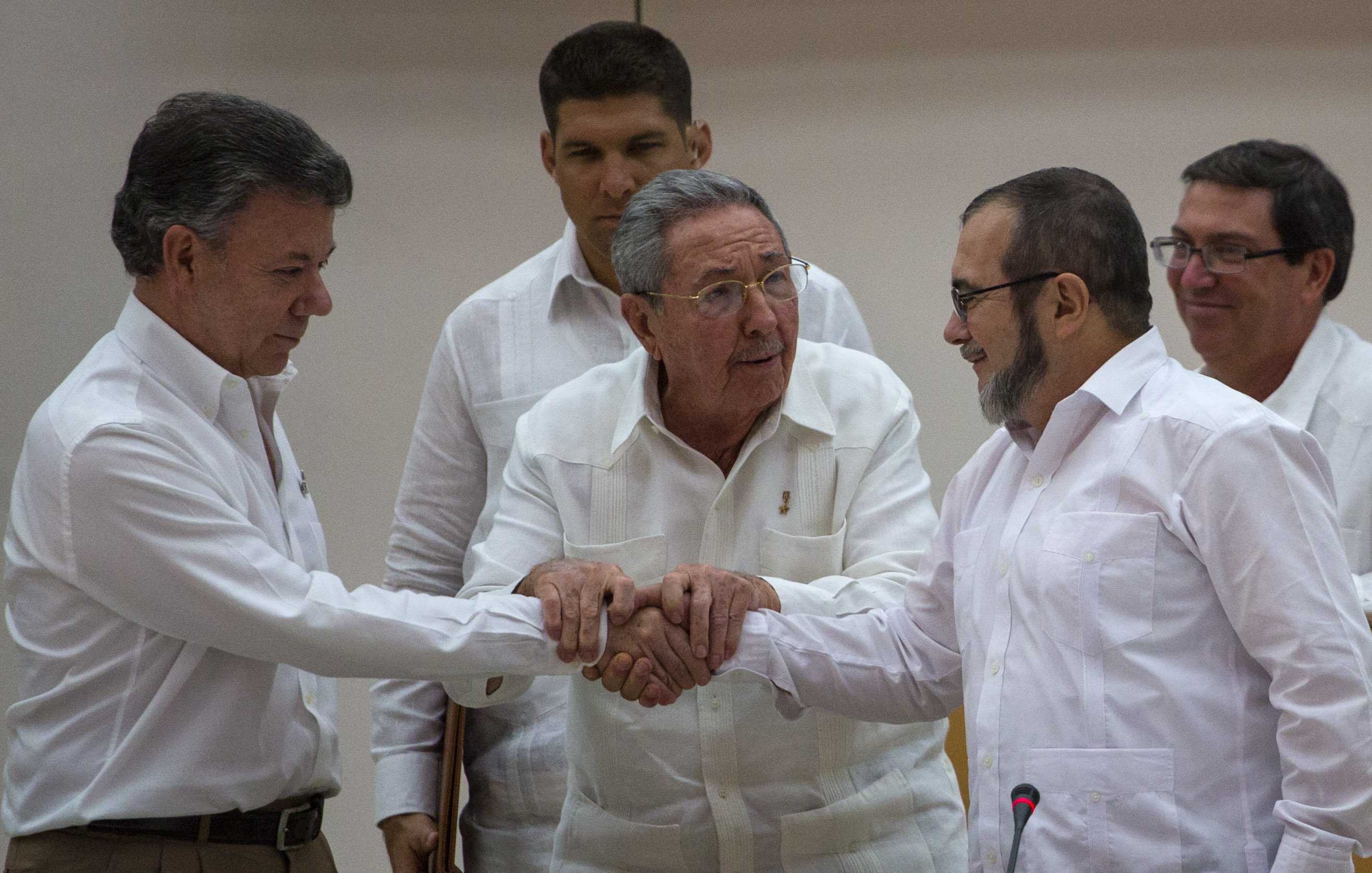 """Cuba's President Raul Castro, center, encourages Colombian President Juan Manuel Santos, left, and Commander the Revolutionary Armed Forces of Colombia or FARC, Timoleon Jimenez, known as """"Timochenko,"""" to shake hands, in Havana, Cuba, Sept. 23, 2015...."""
