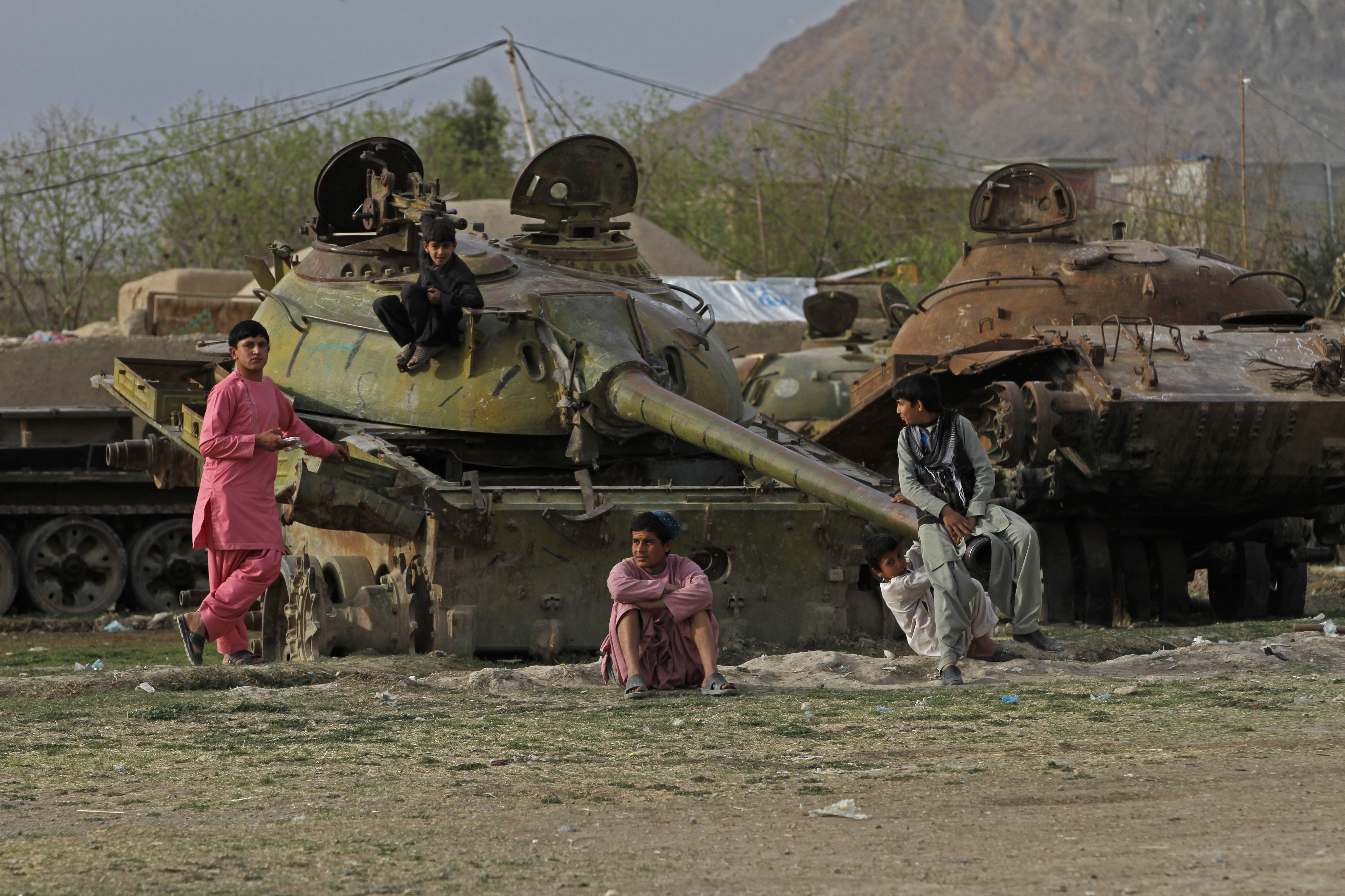 FILE - Afghan boys play on the remains of an old Soviet tank on the outskirts of Kandahar, south of Kabul, Afghanistan, Feb. 21, 2015.