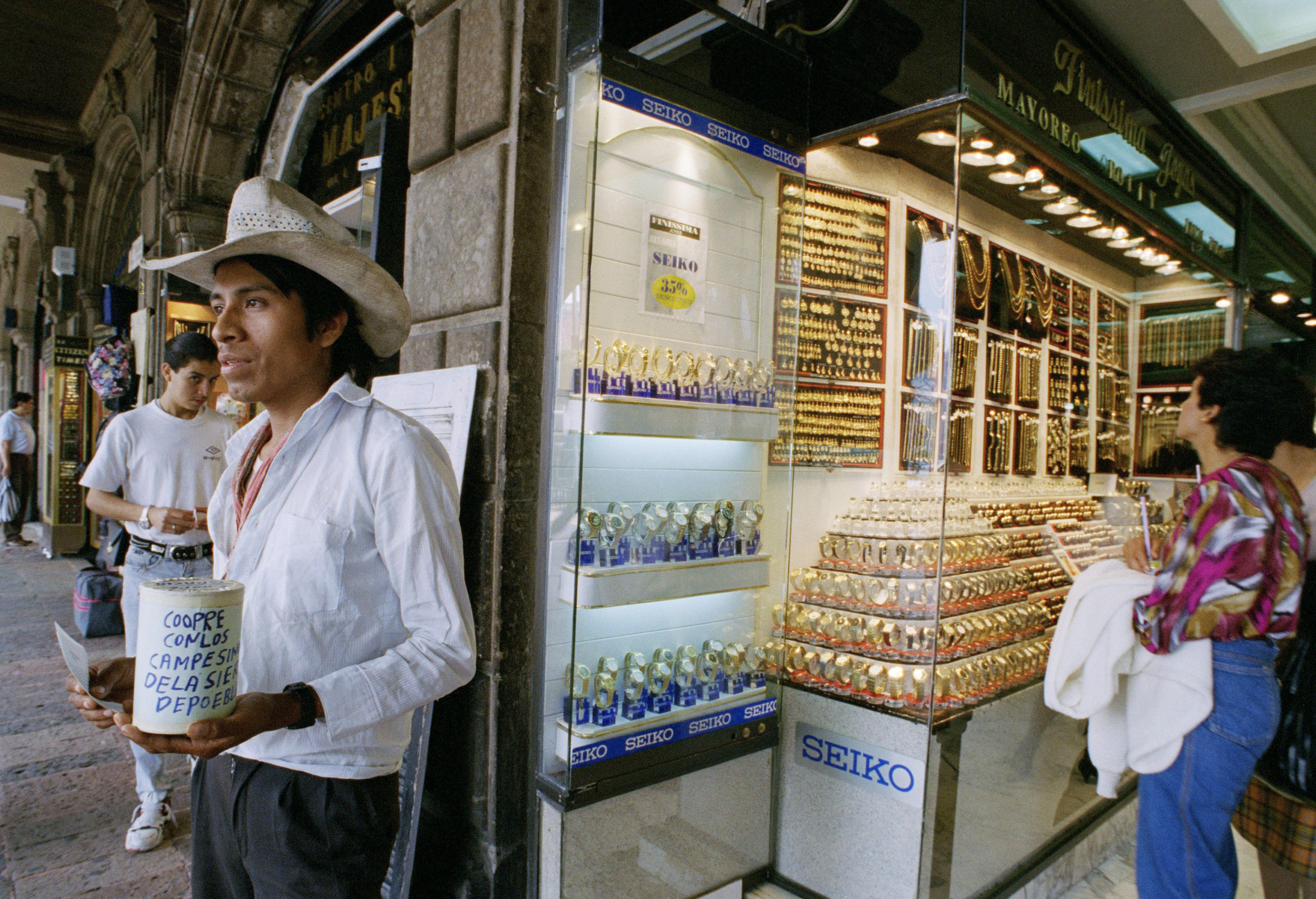 FILE - Manuel Garcia a peasant from the state of Puebla ask for money outside of a jewelry store in Mexico City's main square, Aug. 31, 1995.