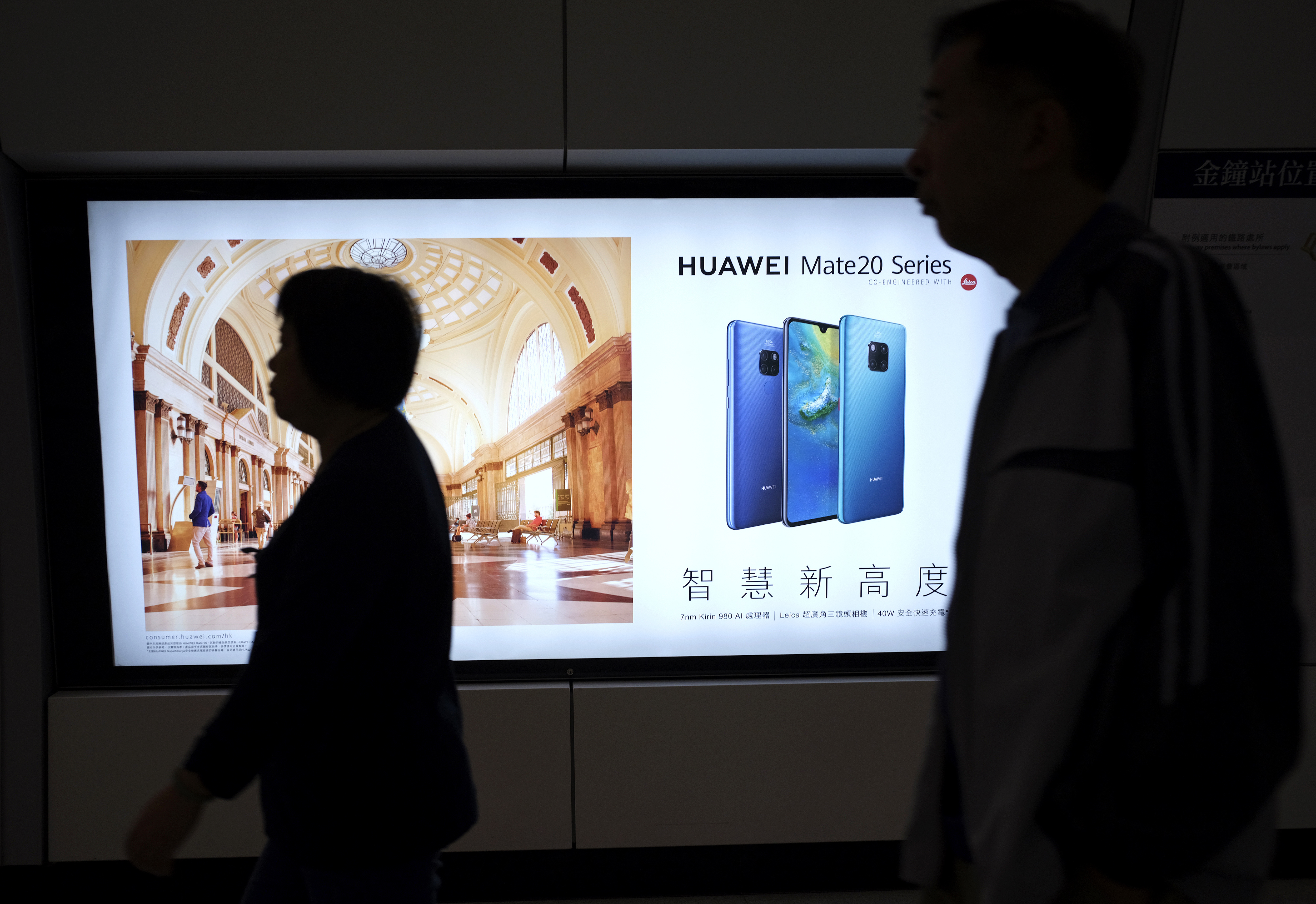 People walk past an advertisement for Huawei at a subway station in Hong Kong, Dec. 5, 2018.