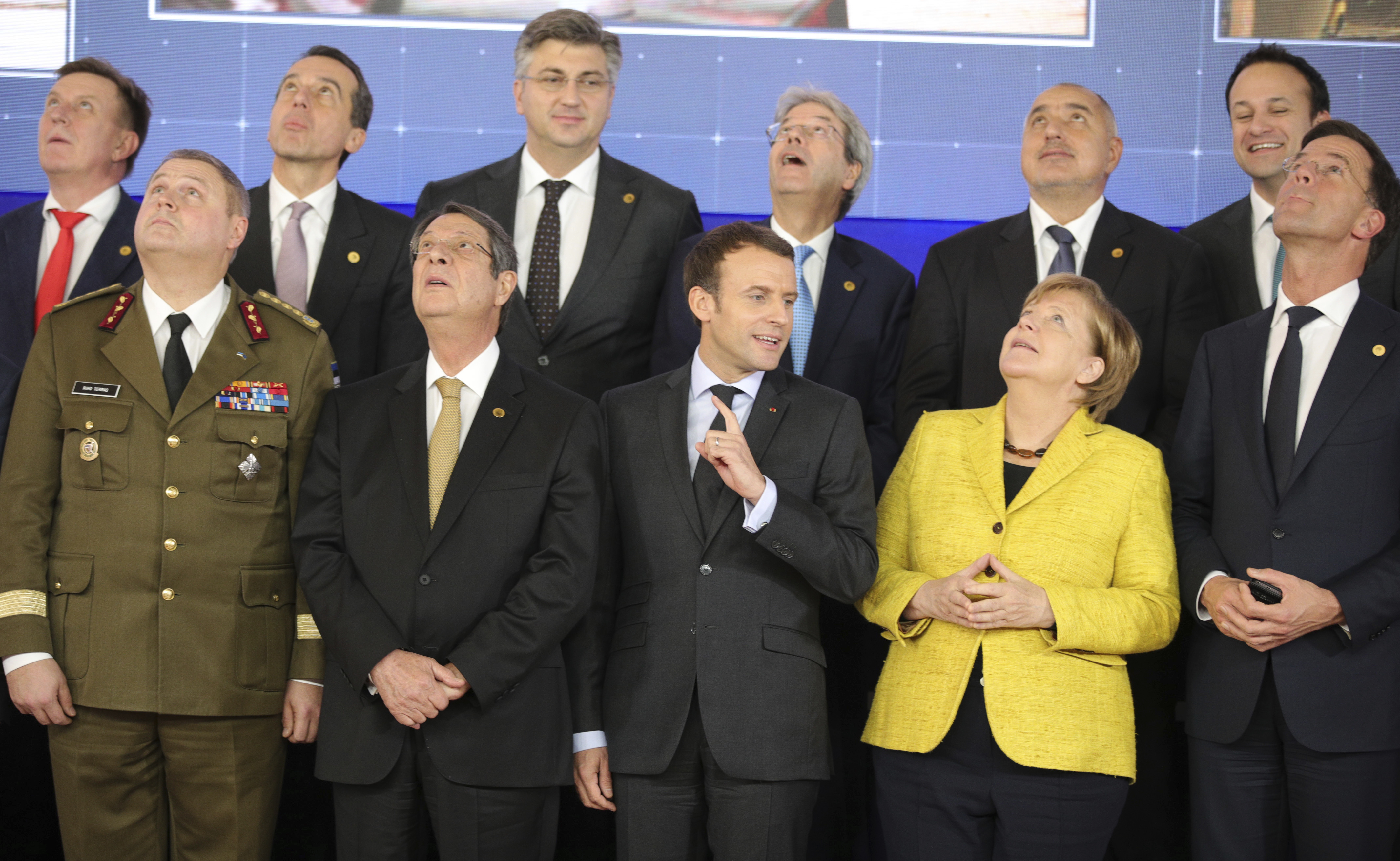 French President Emmanuel Macron, front center, speaks with German Chancellor Angela Merkel, front second right, as they look up at a drone flying above their heads during a group photo at an EU summit at the Europa building in Brussels, Dec. 14, 201...
