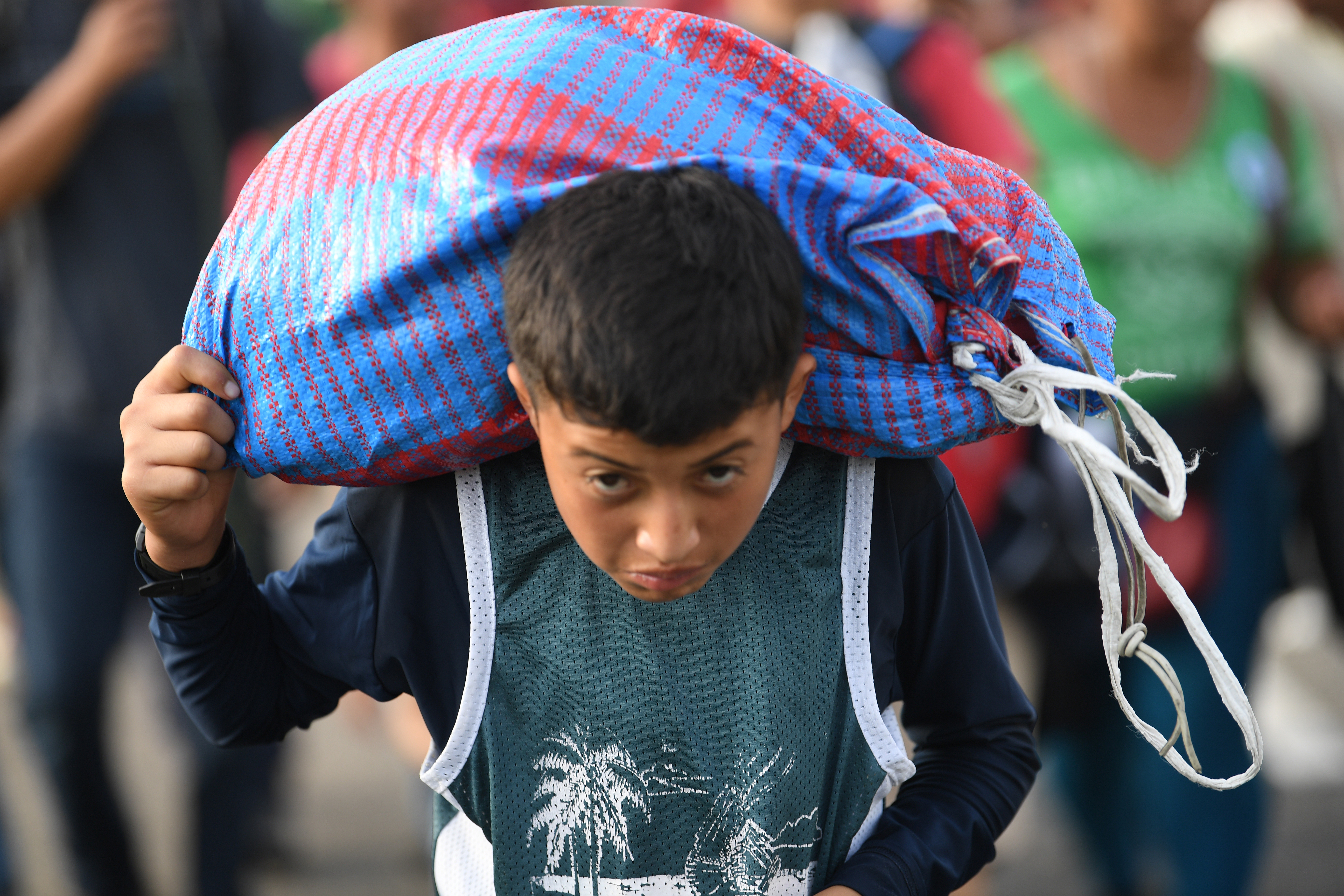 A Honduran migrant boy carries a bag as he takes part in a caravan heading to the US on the road linking Ciudad Hidalgo and Tapachula, Chiapas state, Mexico, Oct. 21, 2018.