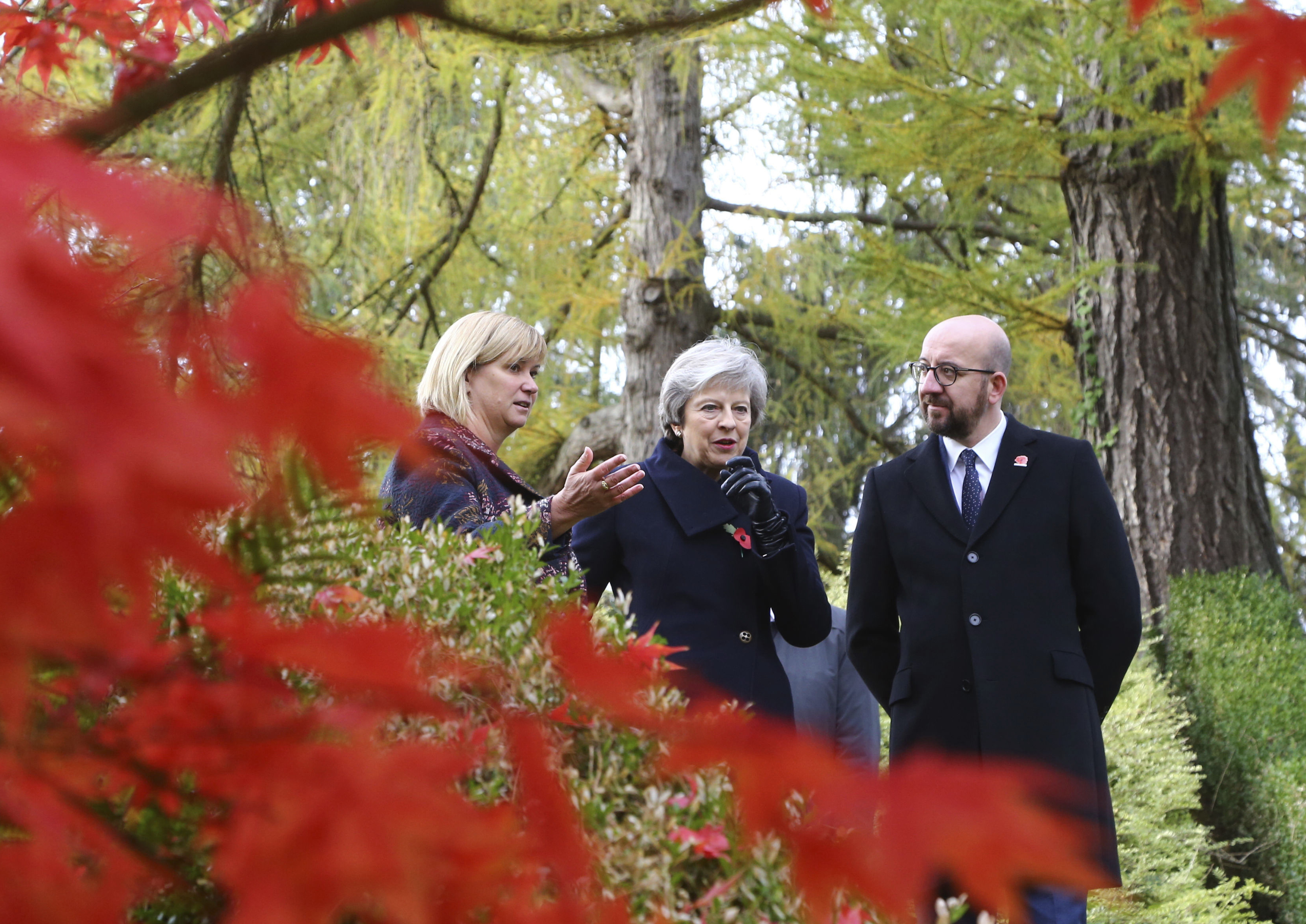 Britain's Prime Minister Theresa May, Belgian Prime Minister Charles Michel, right, and Liz Sweet, Director, External Relations, Western Europe Area, Commonwealth War Graves Commission, left, walk through the St Symphorien Military Cemetery in Mons, ...