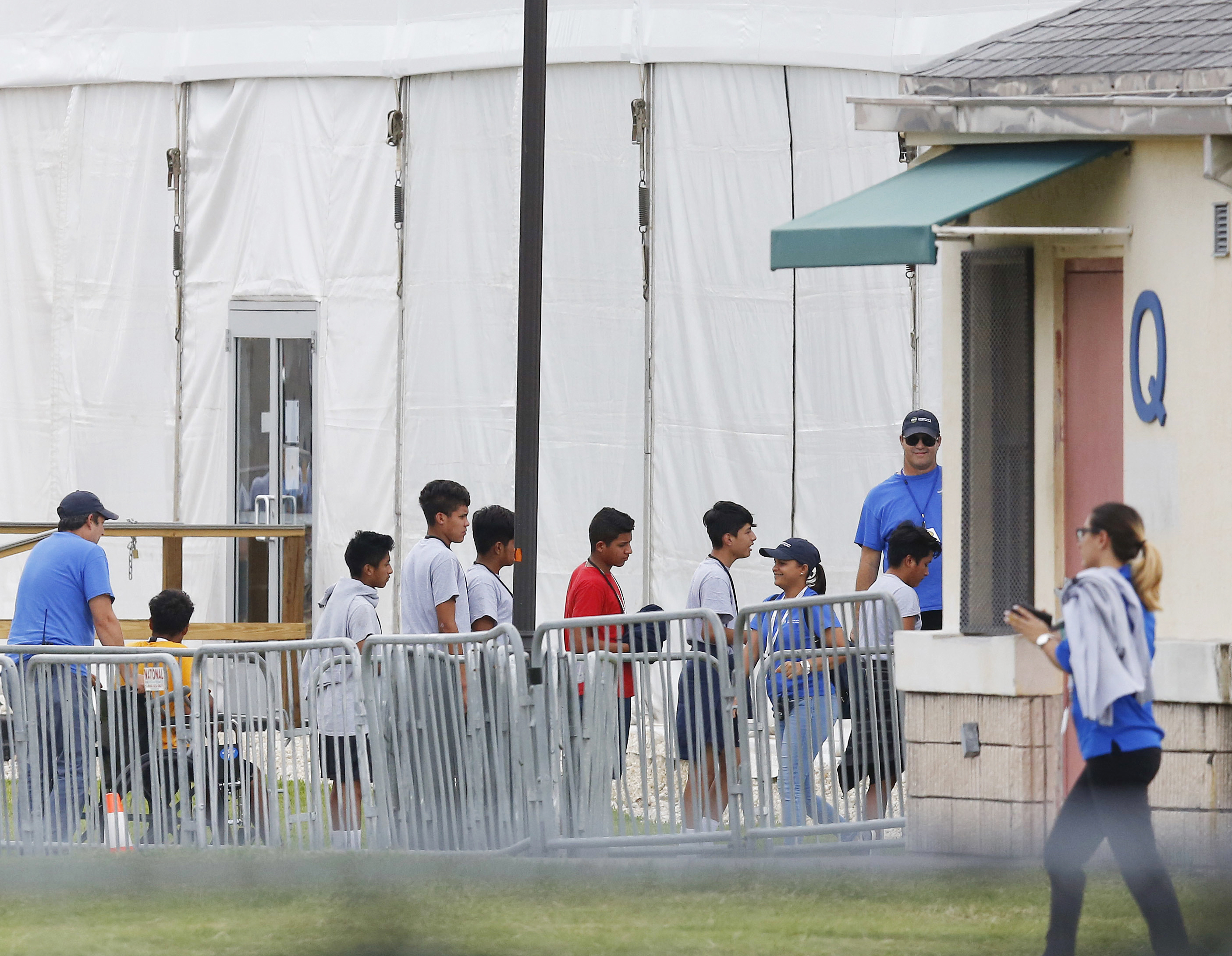FILE - In this June 20, 2018, file photo, immigrant children walk in a line outside the Homestead Temporary Shelter for Unaccompanied Children, a former Job Corps site that now houses them in Homestead, Florida.