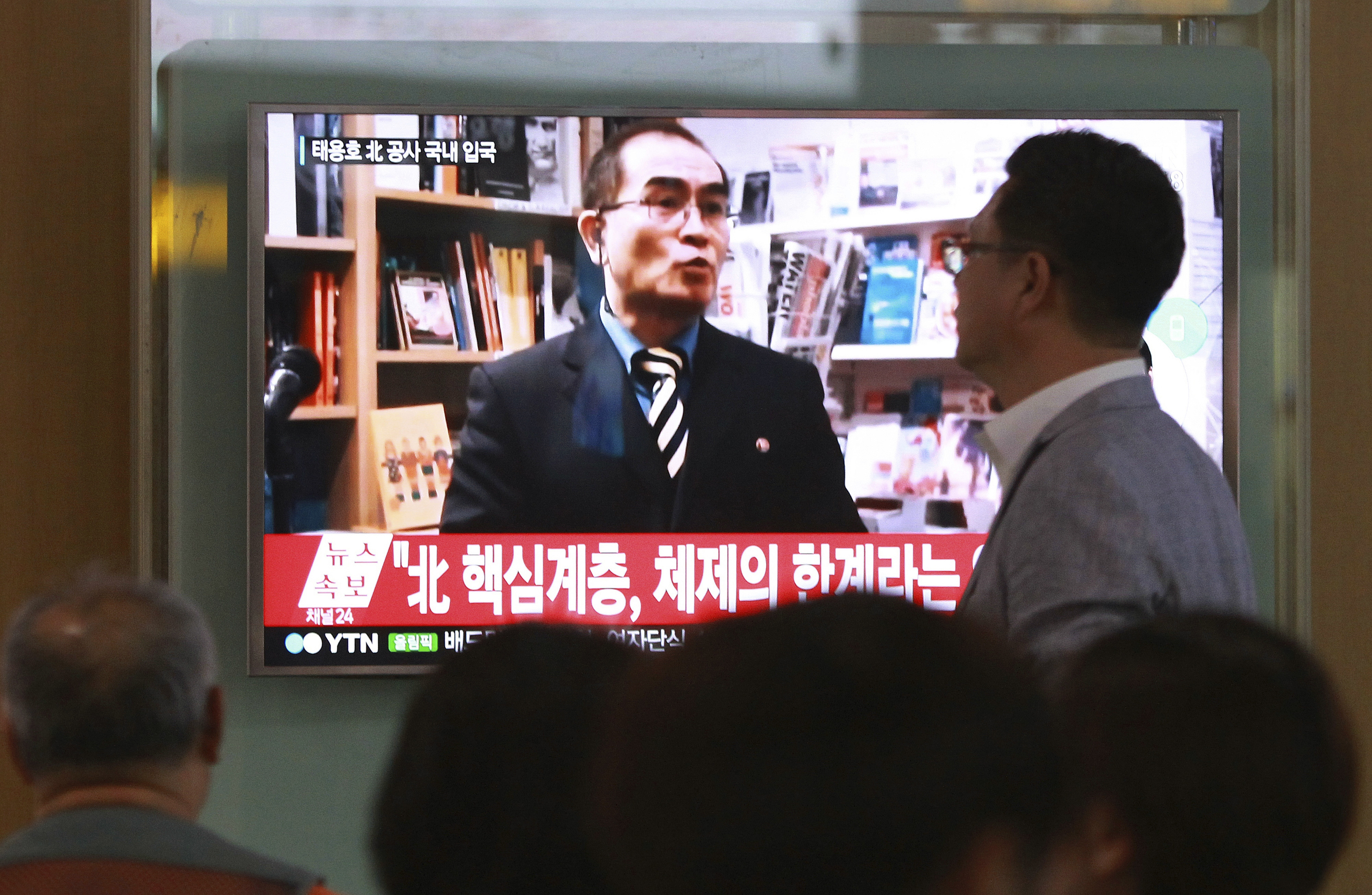 People watch a TV news program showing a file image of Thae Yong Ho, a high-profile North Korean defector, at Seoul Railway Station in Seoul, South Korea, Aug. 17, 2016