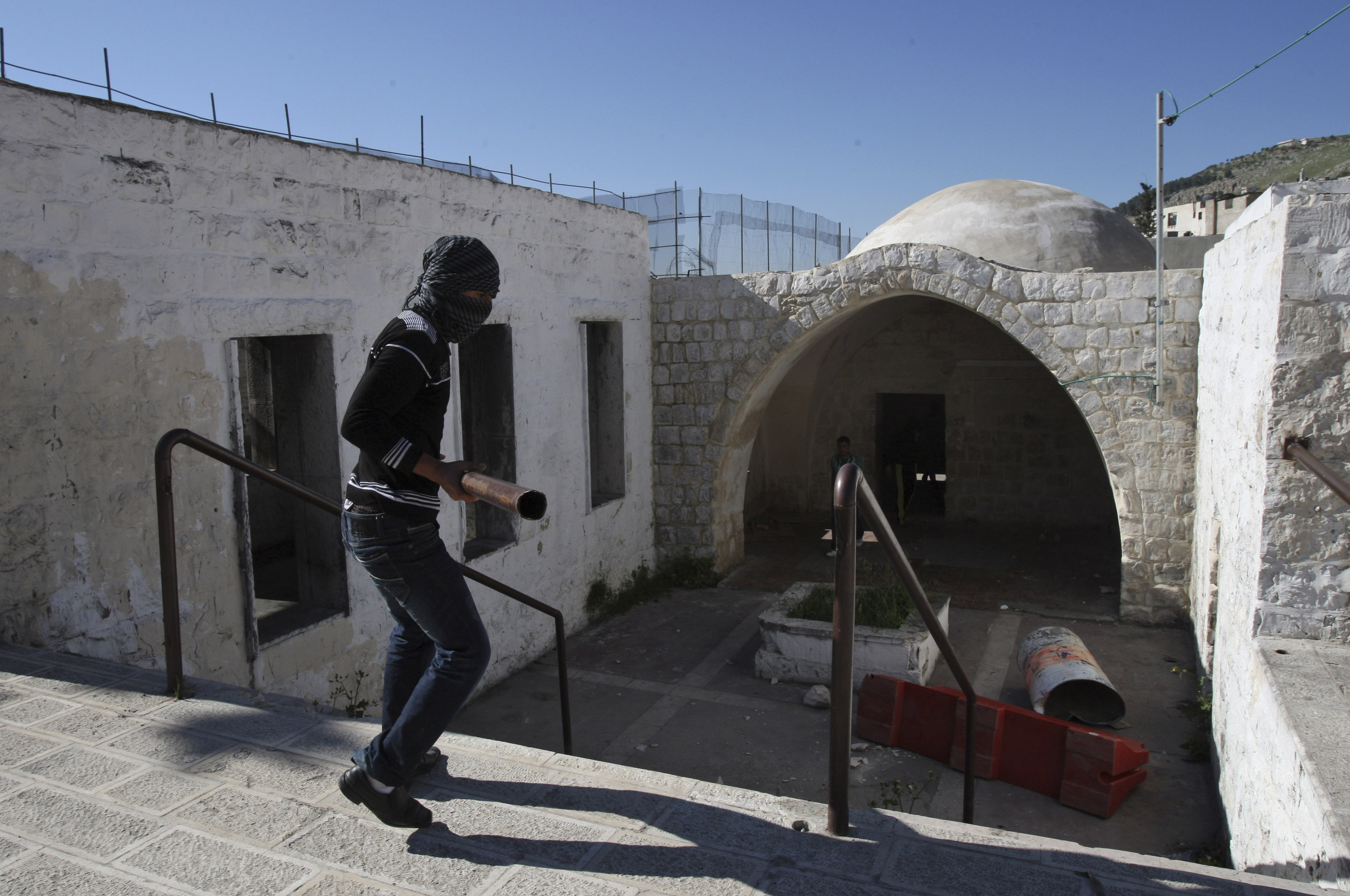 FILE - A masked Palestinian youth walks into  Joseph's Tomb during clashes with Israeli troops nearby, in the West Bank city of Nablus, April 24, 2011.