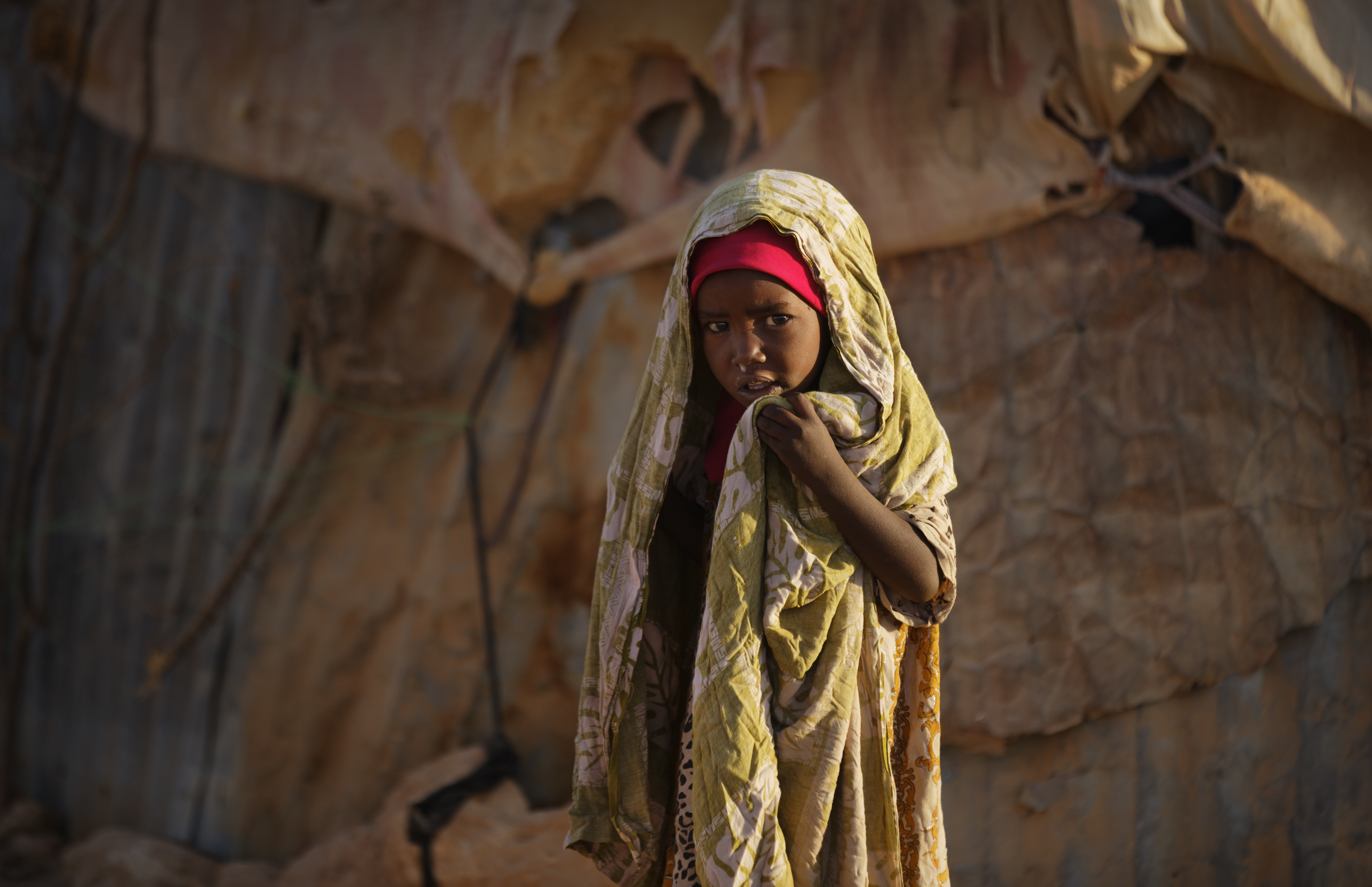 A young Somali girl stands outside her makeshift hut at a camp of people displaced from their homes elsewhere in the country by the drought, shortly after dawn in Qardho, Somalia, March 9, 2017.