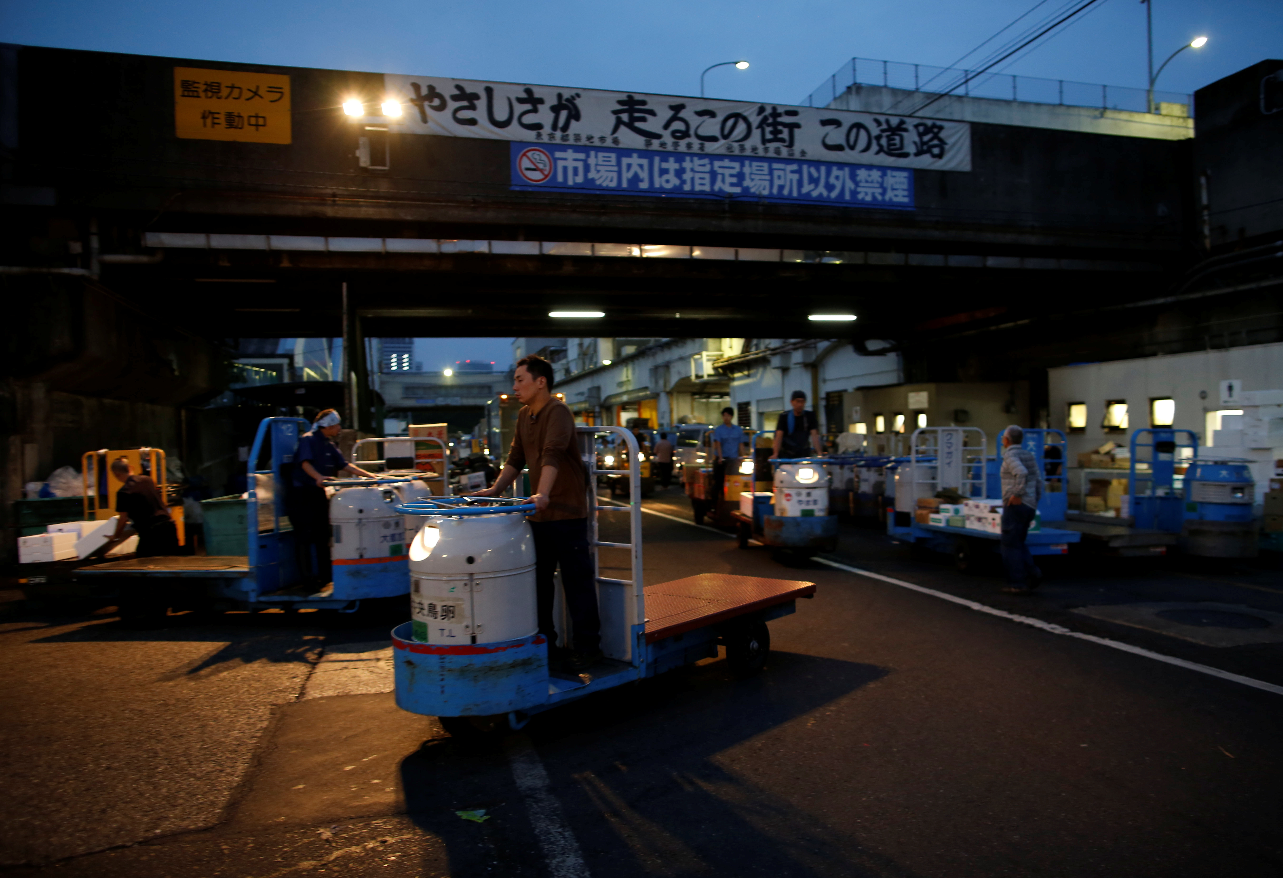 Workers drive vehicles known as turret trucks at the Tsukiji fish market in Tokyo, Japan, Sept. 25, 2018.