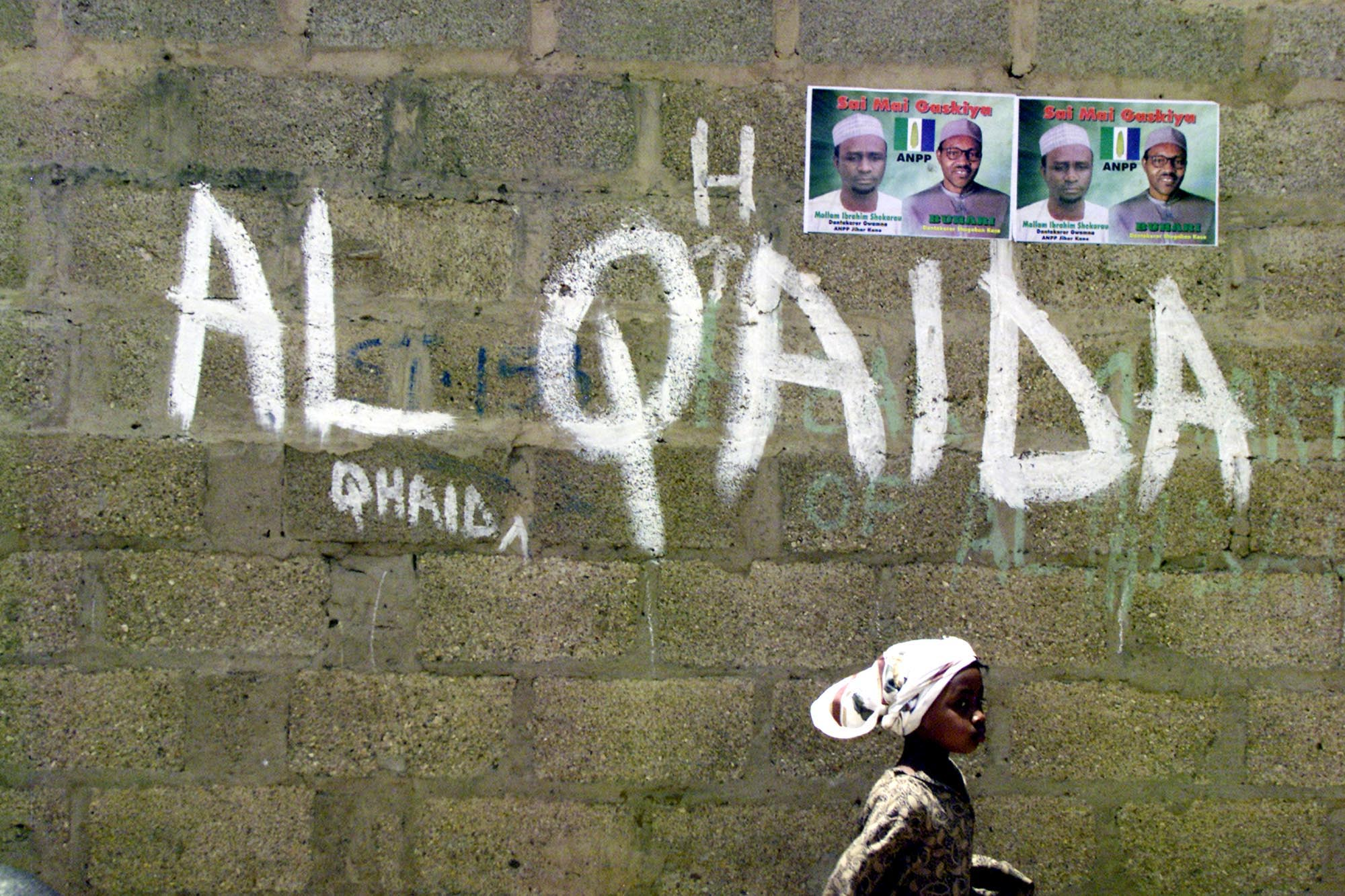 A girl walks past a wall with graffiti about the al-Qaida network in a Muslim area of the northern city of Kano, Nigeria, (File photo).