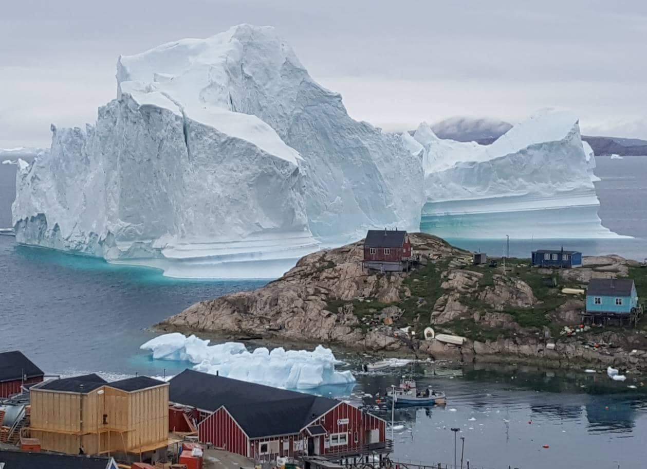 A giant iceberg is seen behind an Innaarsuit settlement, Greenland, July 12, 2018.