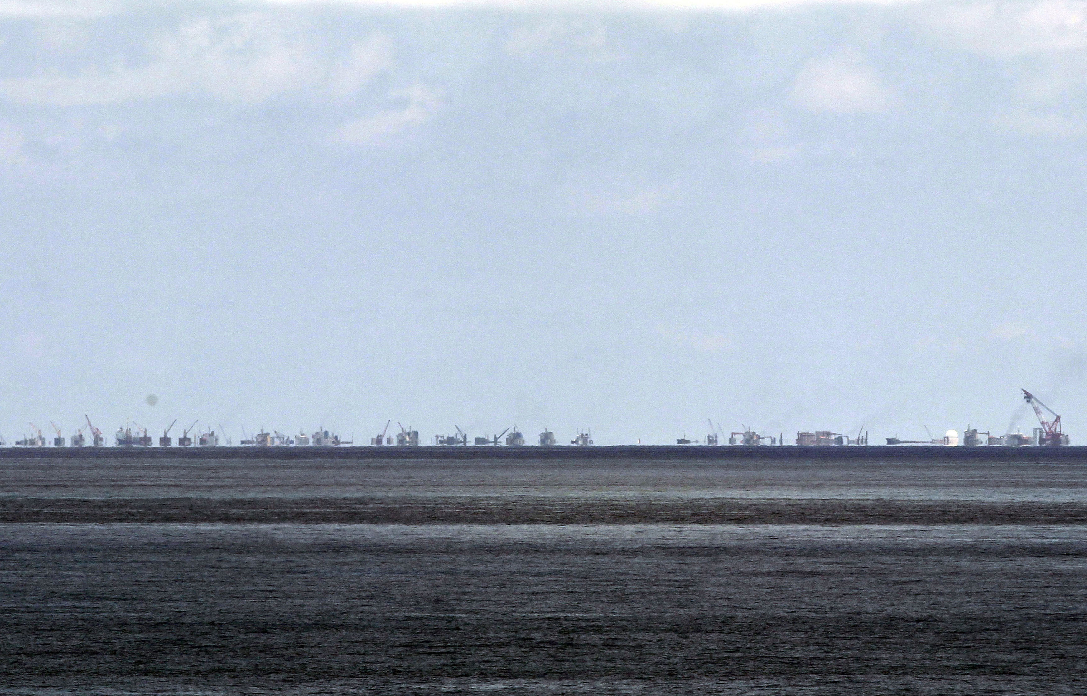 FILE - The alleged on-going reclamation of Subi Reef by China is seen from Pag-asa Island in the Spratly Islands in the South China Sea, western Palawan Province, Philippines, May 11, 2015.