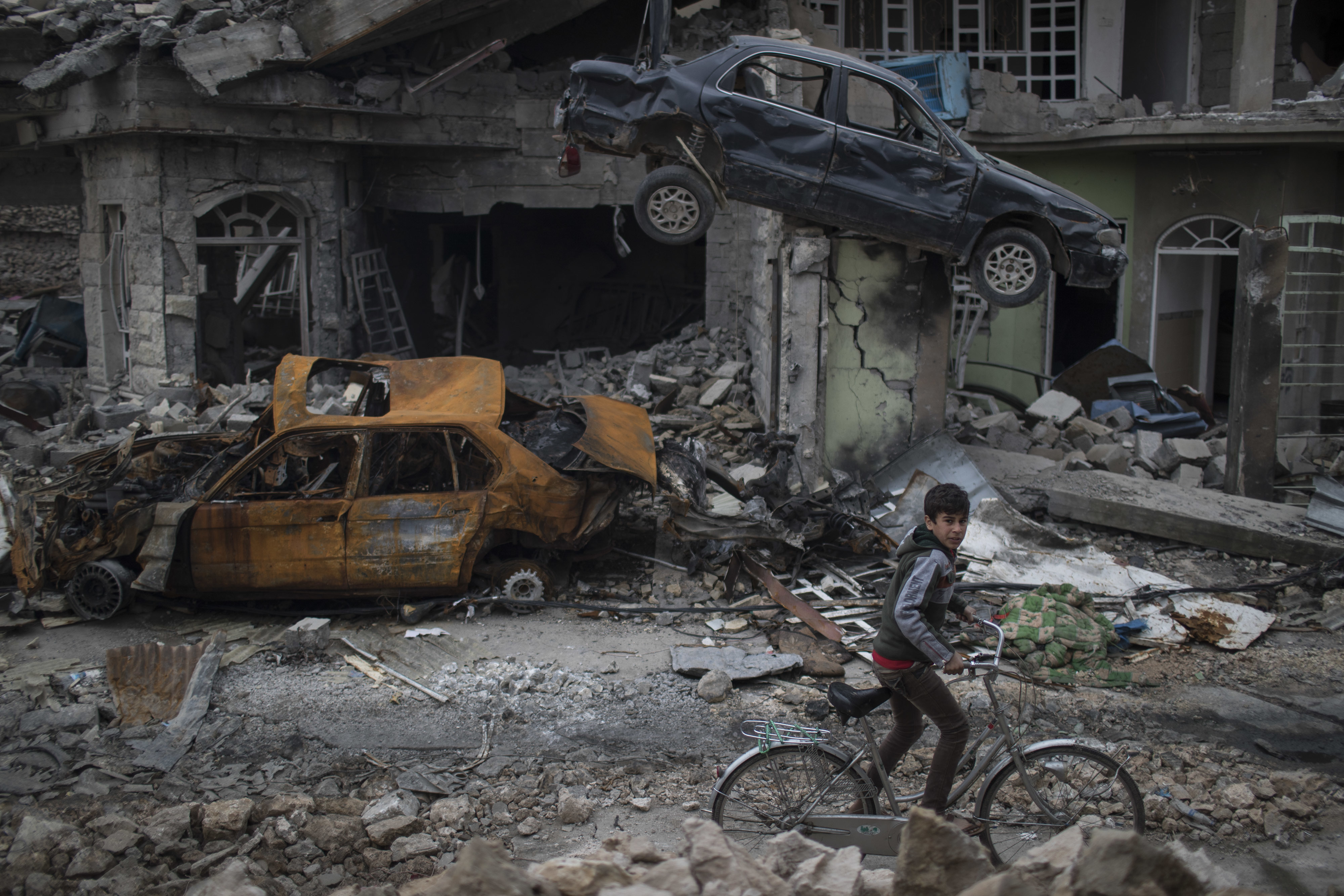 FILE - A boy rides his bike past destroyed cars and houses in a neighborhood recently liberated by Iraqi security forces on the western side of Mosul, Iraq, March 19, 2017.