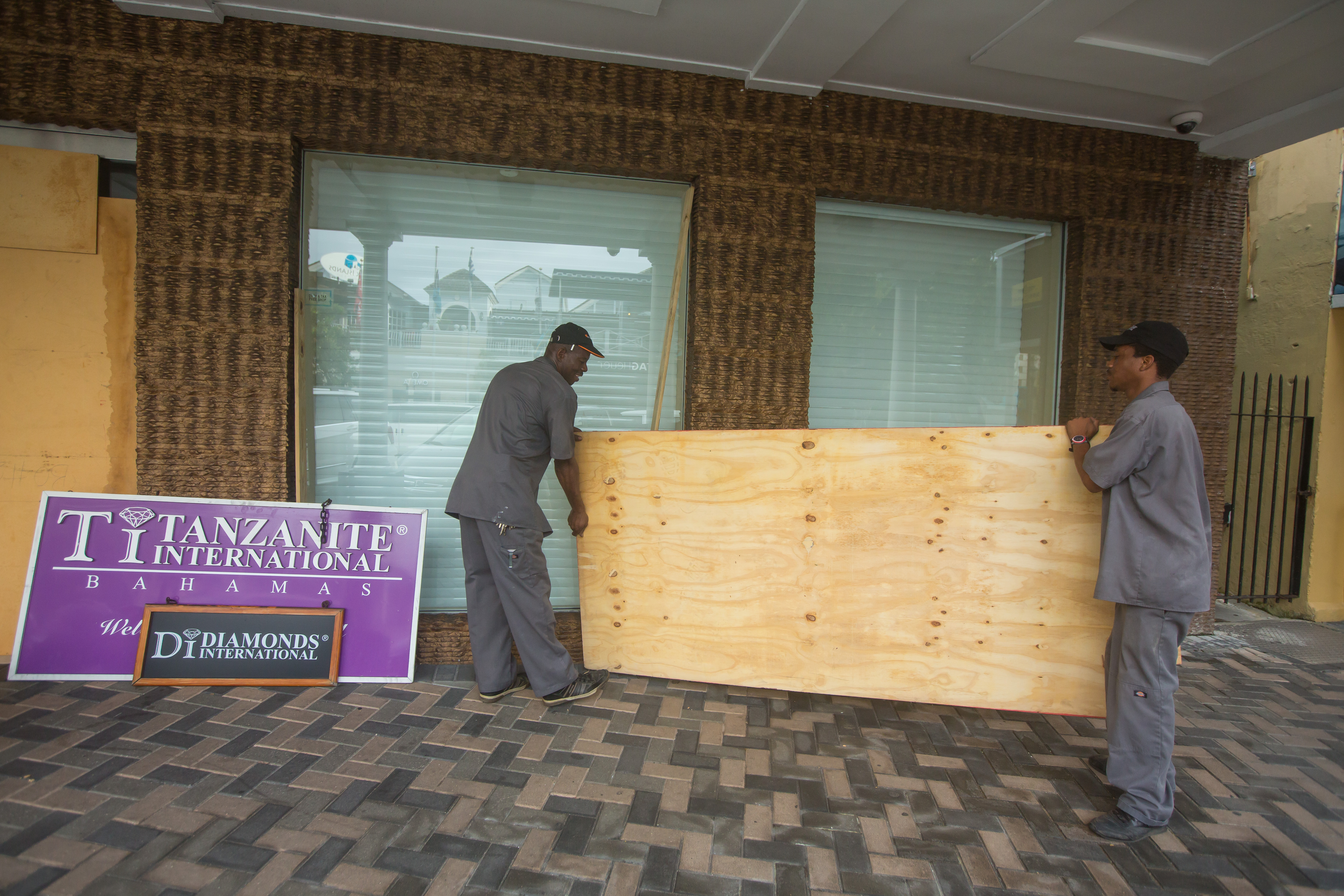 Perry Williams, 47, left, and Alaric Nixon, 28, carry a sheet of plywood as they cover the windows of the Diamond's International store, in preparation for the arrival of hurricane Joaquin in Nassau, Bahamas, Thursday, Oct. 1, 2015.