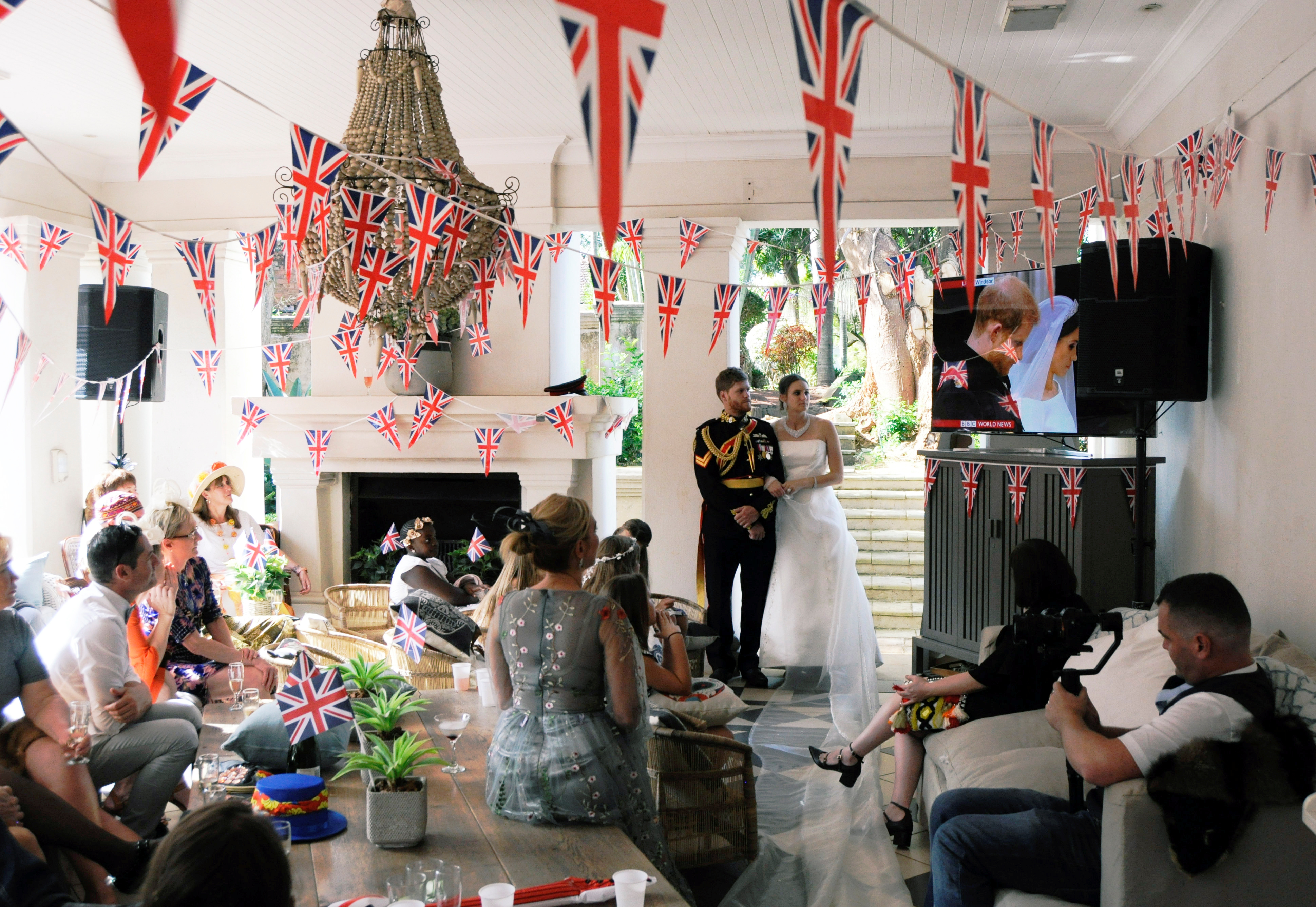 People watch Britain's Prince Harry and Meghan Markle during their wedding on television at a party in Durban, South Africa, May 19, 2018.