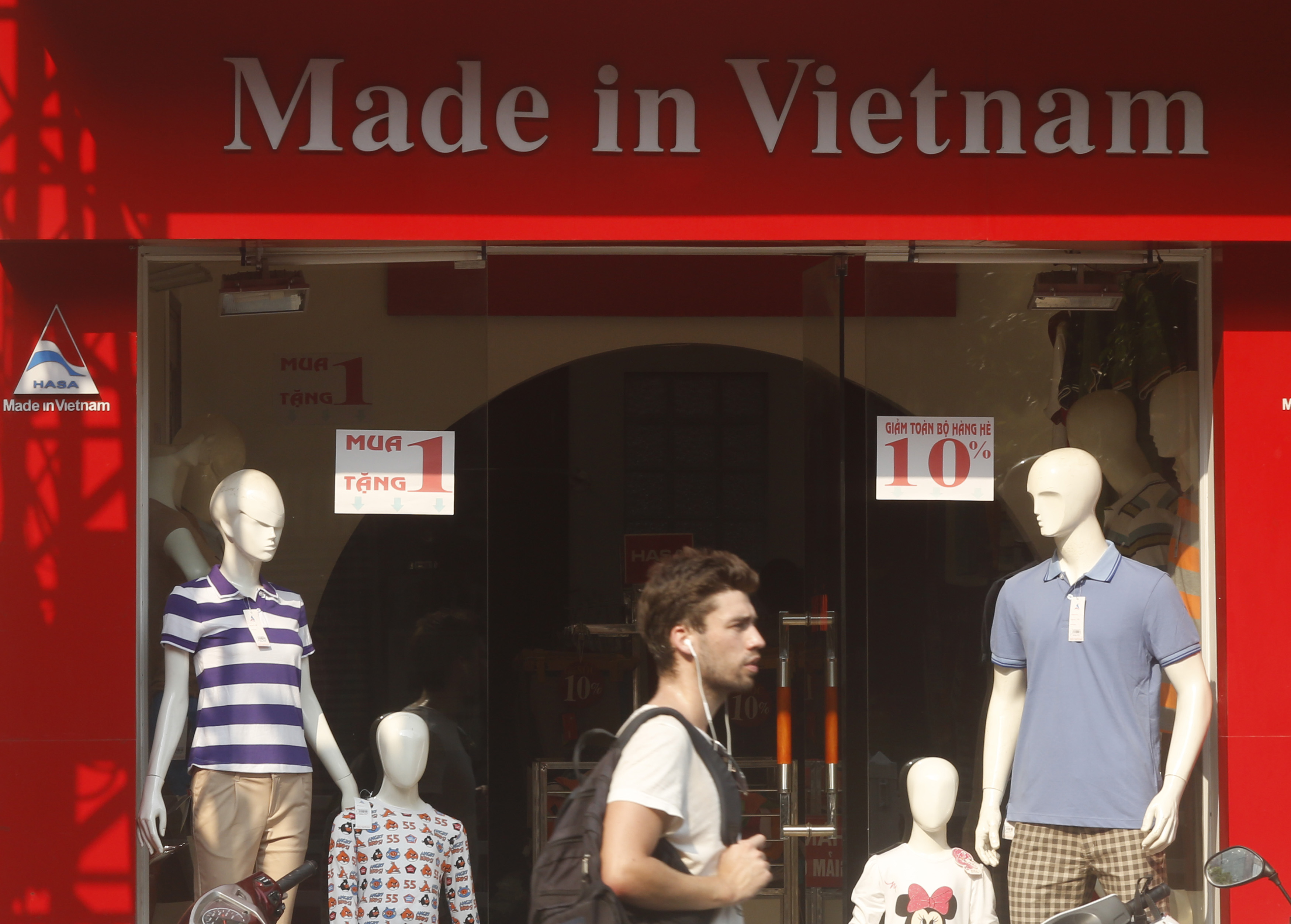 A tourist walks past a clothes shop in Hanoi October 3, 2014. Growth in exports driven by manufacturing could give Vietnam a trade surplus of $1.5 billion this year, far surpassing its forecast of $500 million in July, according to the country's trad...