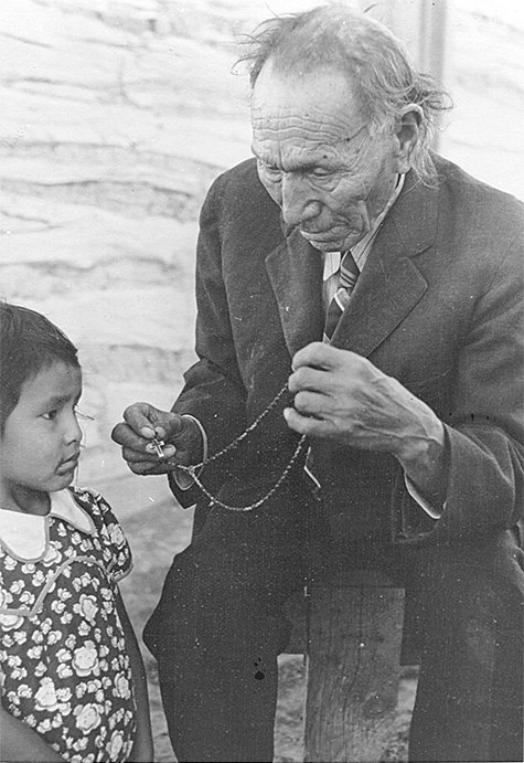 Nicholas Black Elk teaching an unidentified child the rosary, ca. 1940. Courtesy Red Cloud Indian School and Marquette University. Holy Rosary Mission – Red Cloud Indian School Records, ID MUA_HRM_RCIS_00040
