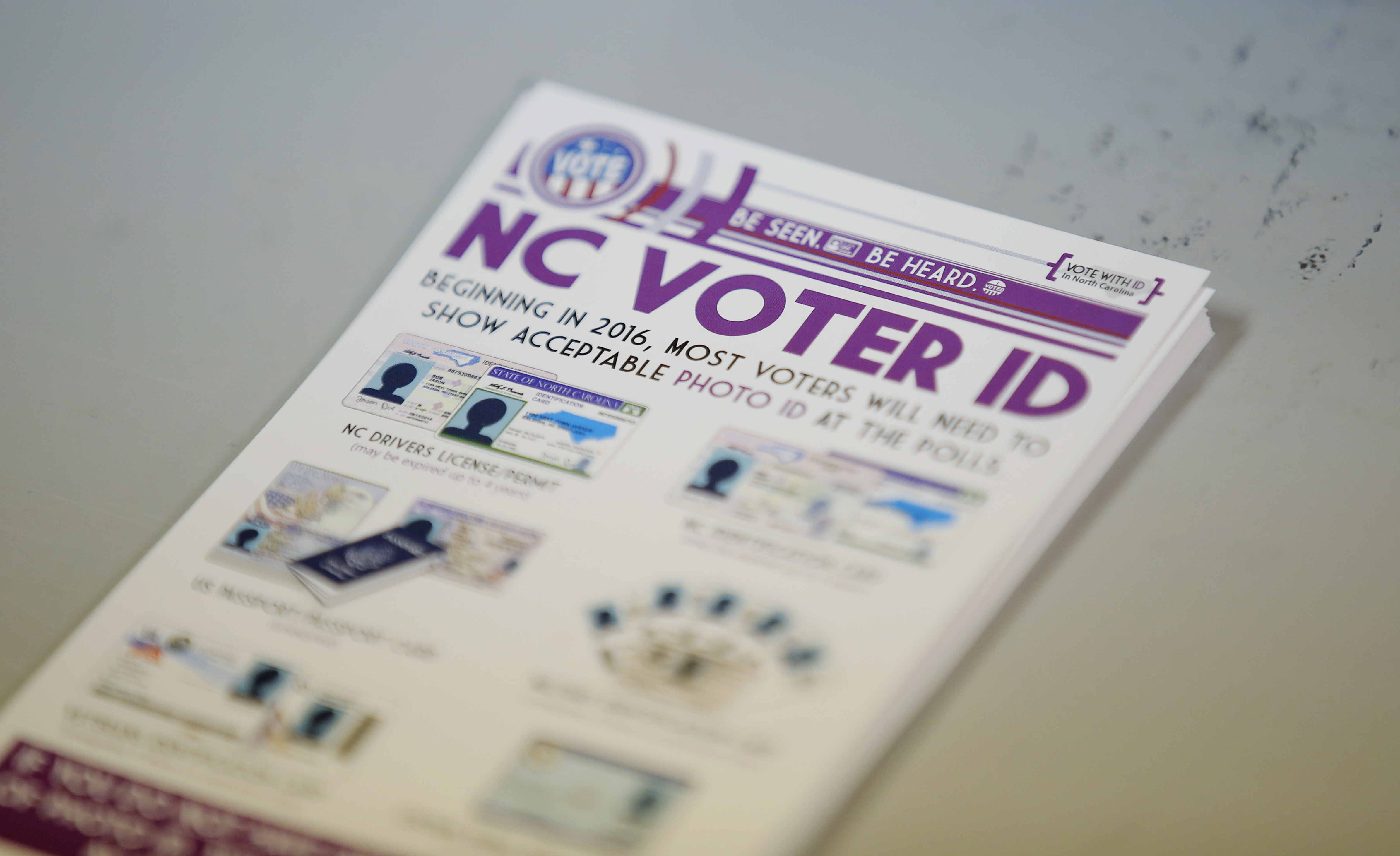 """A pile of government pamphlets explaining North Carolina's controversial """"Voter ID"""" law sits on table at a polling station as the law goes into effect for the state's presidential primary in Charlotte, North Carolina, March 15, 2016."""