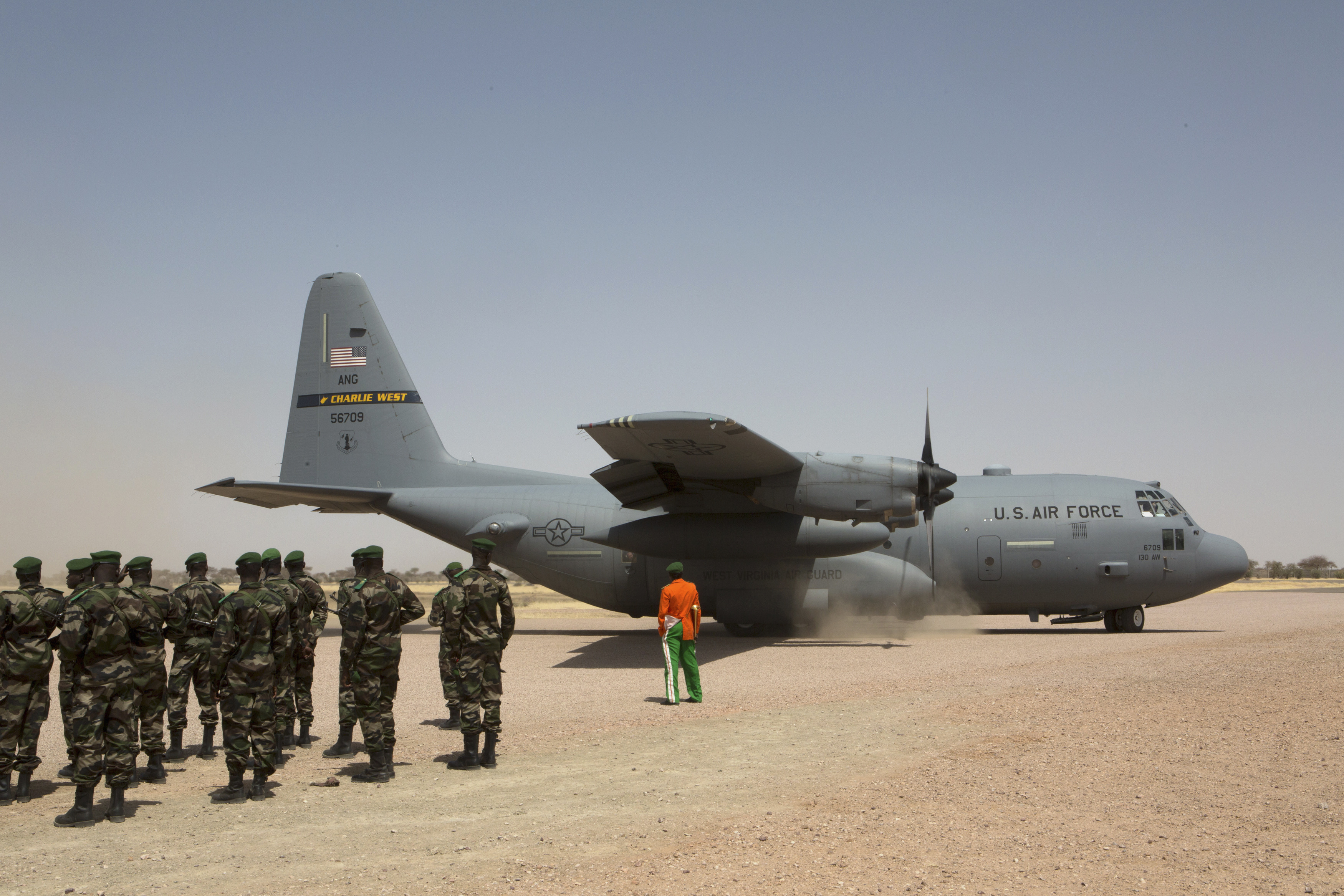 FILE - A C-130 U.S. Air Force plane taxis as Nigerien soldiers stand in formation during the Flintlock 2014 military exercise in Diffa, Niger, March 8, 2014.