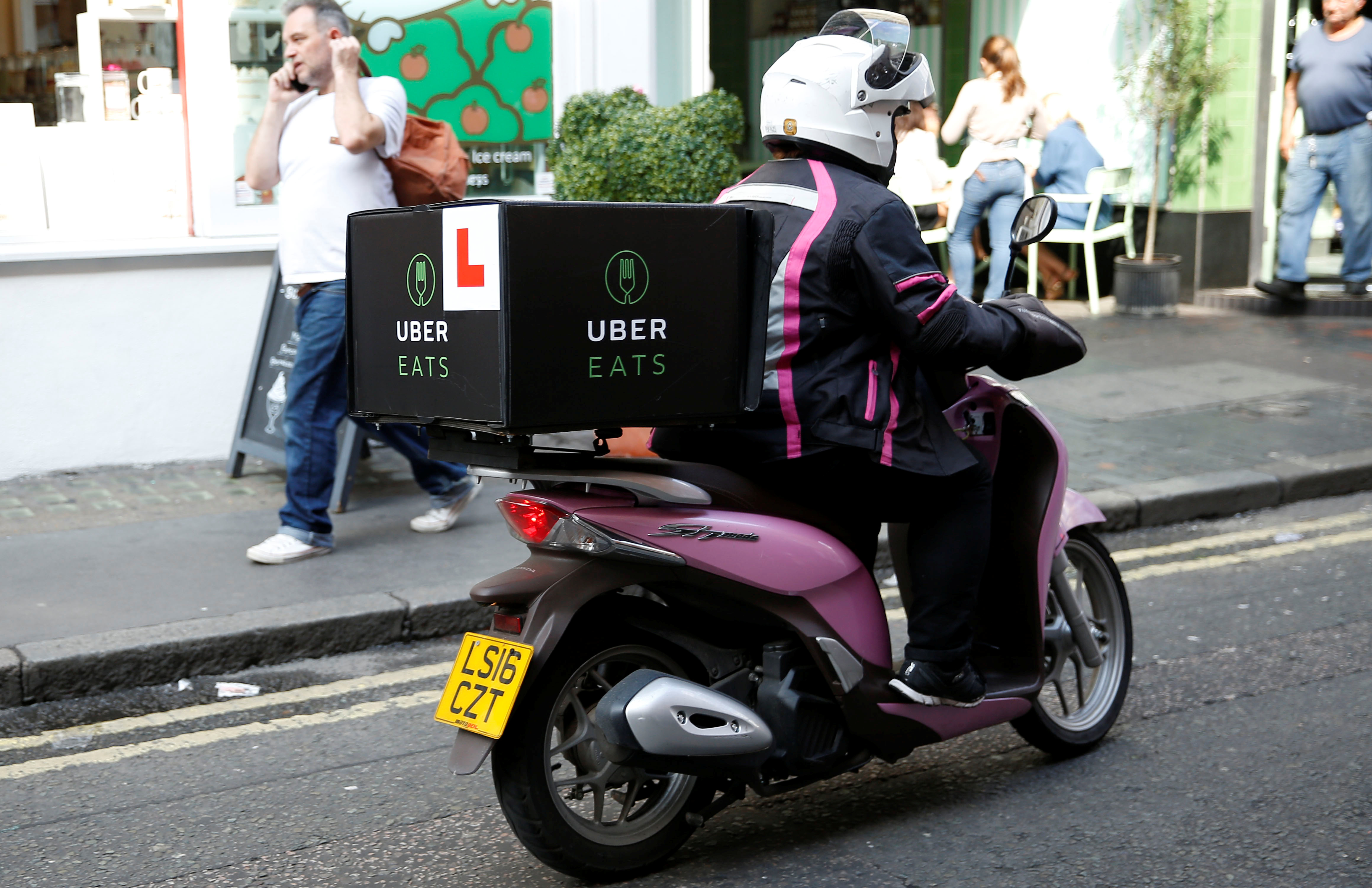 An UberEATS food delivery courier rides her scooter in London on September 7, 2016.