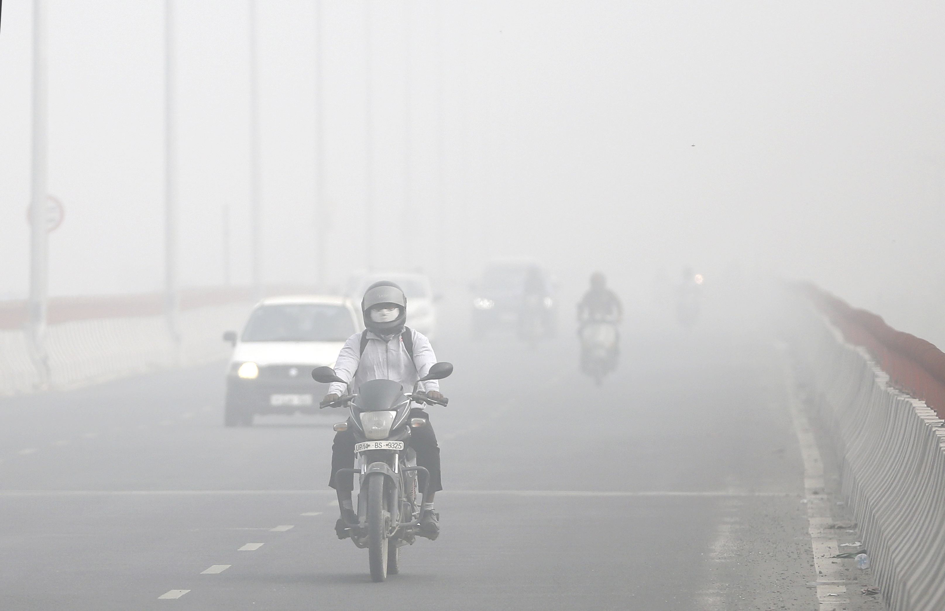 Motorists drive surrounded by smog, in New Delhi, India, Nov. 8, 2017.