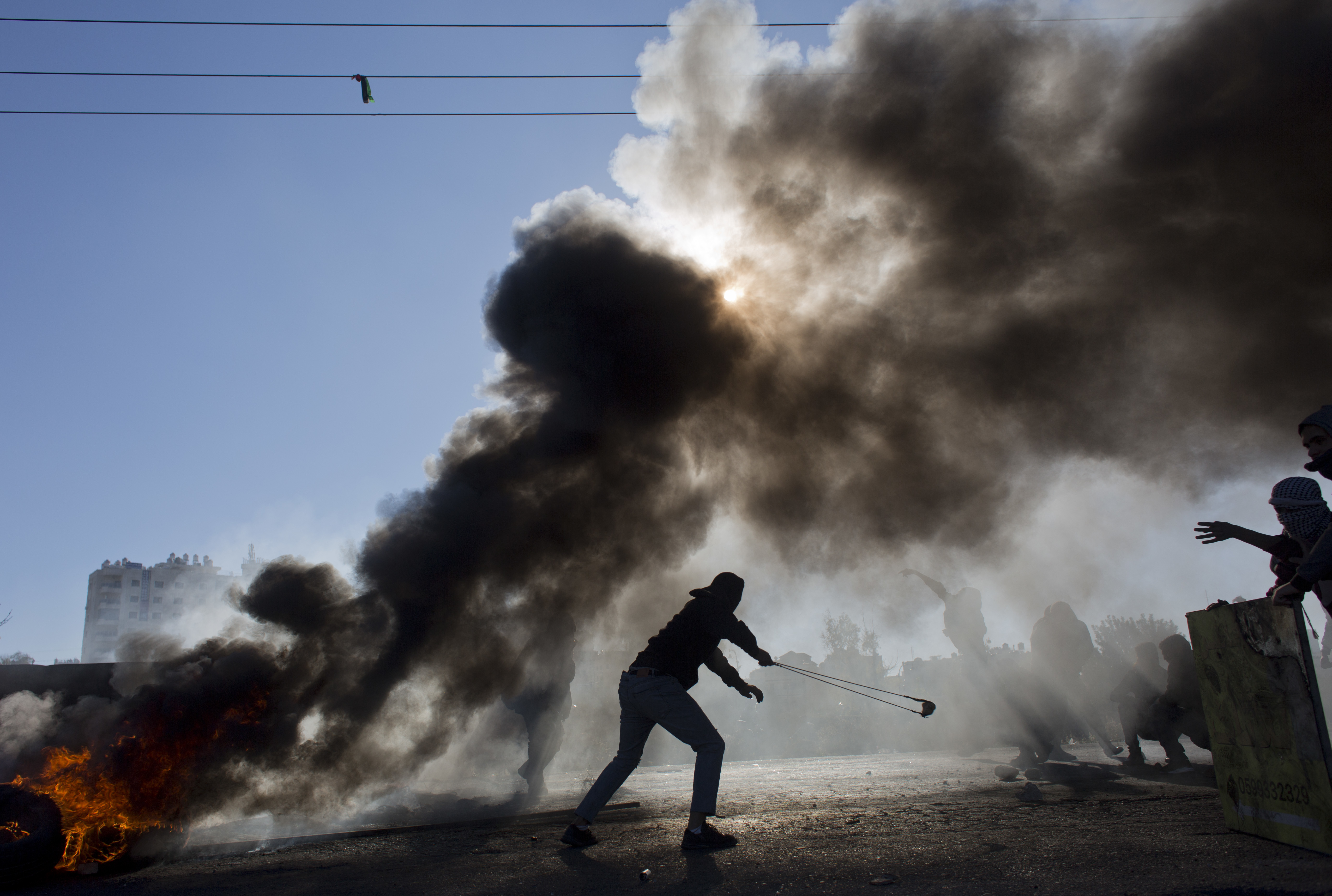 FILE - Palestinian protesters burn tires and clash with Israeli troops following protests against U.S. President Donald Trump's decision to recognize Jerusalem as the capital of Israel, in the West Bank city of Ramallah, Dec. 8, 2017.