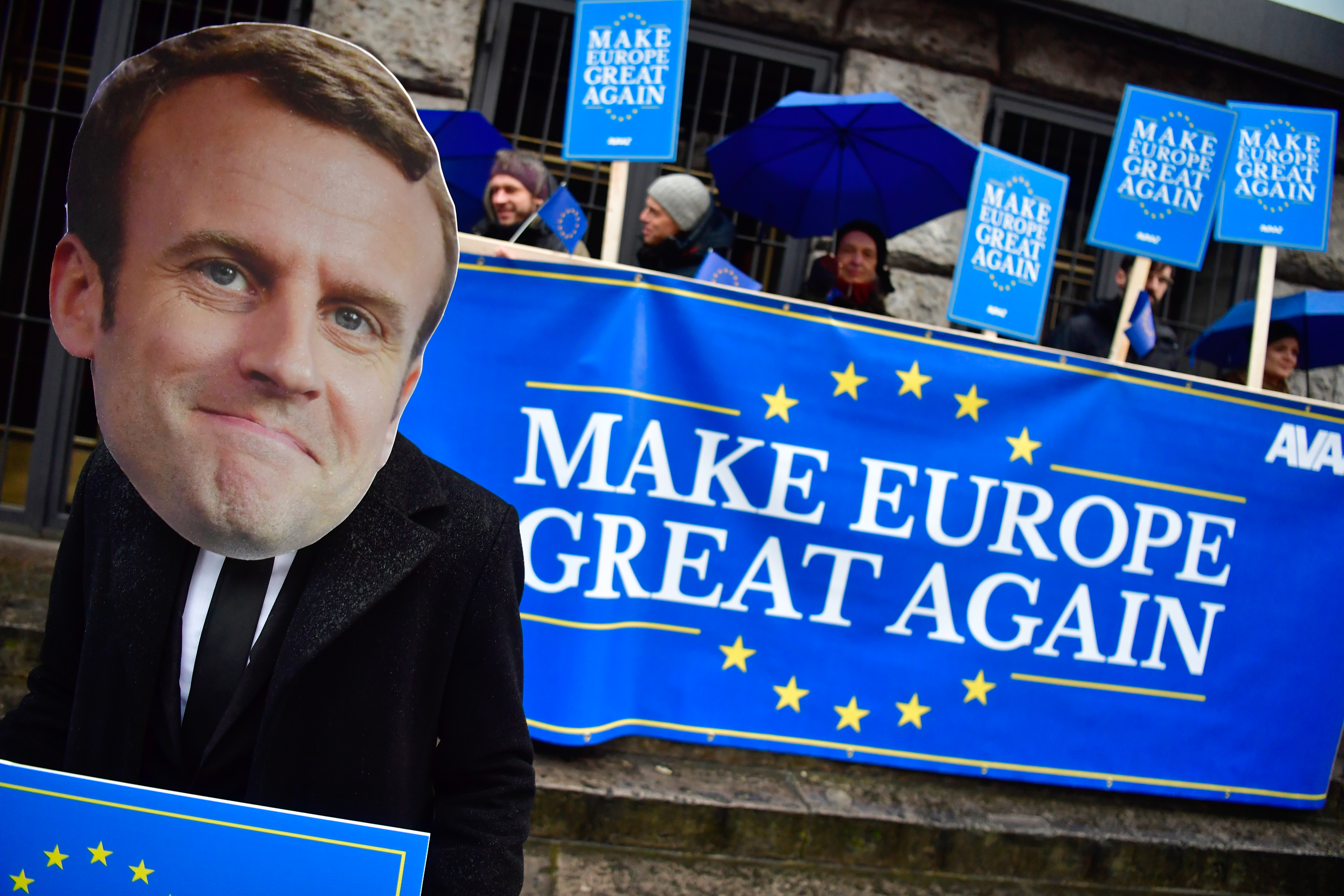 """Activists of the Avaaz civic organization wear a mask of French President Emmanuel Macron and hold up posters and a banner reading """"Make Europe Great Again"""" as they demonstrate in Berlin in front of the venue where are meeting the leaders of Germany'..."""