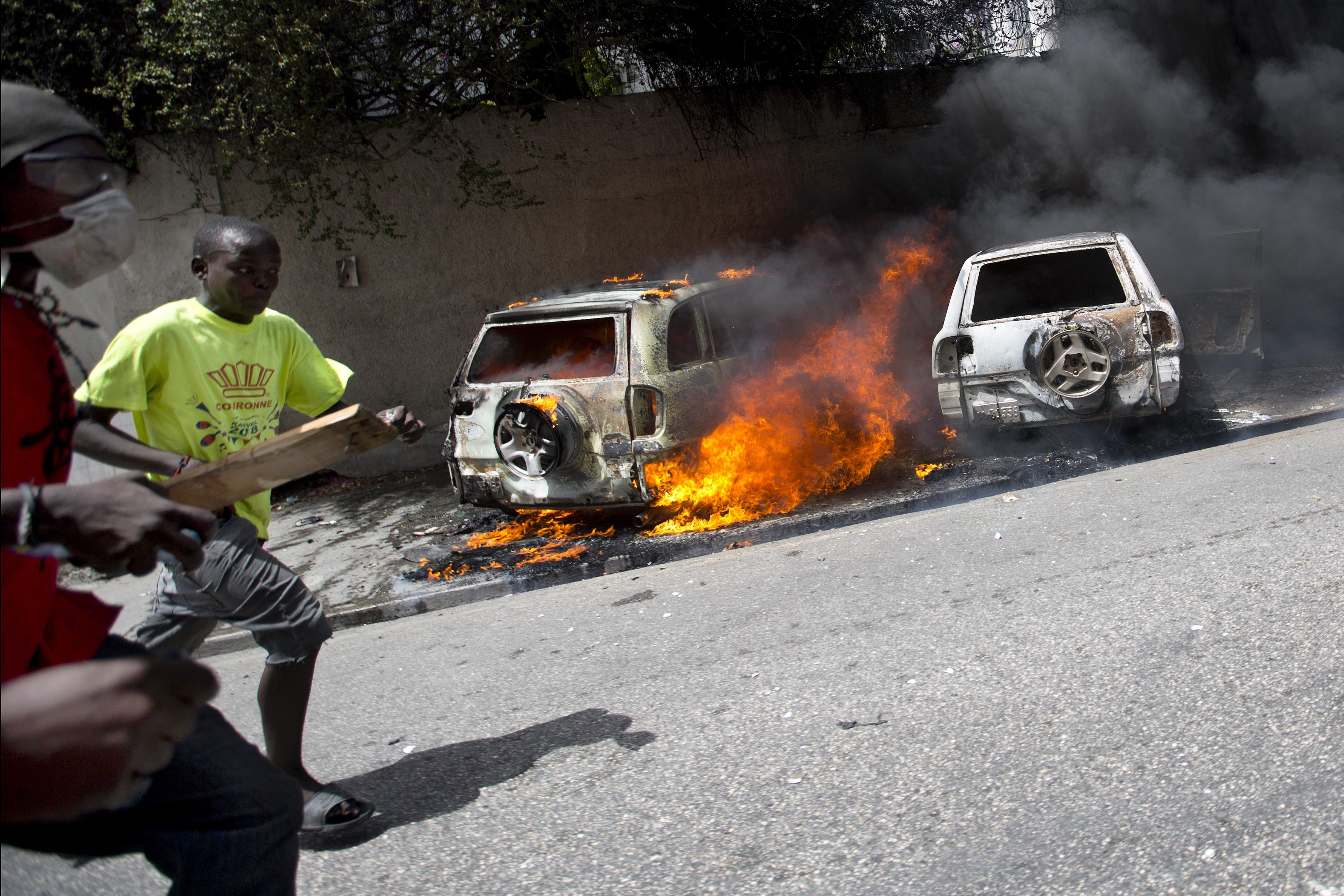 People run after cars were set on fire near a Best Western hotel during protests over a fuel price increase in Port-au-Prince, Haiti, July 7, 2018.