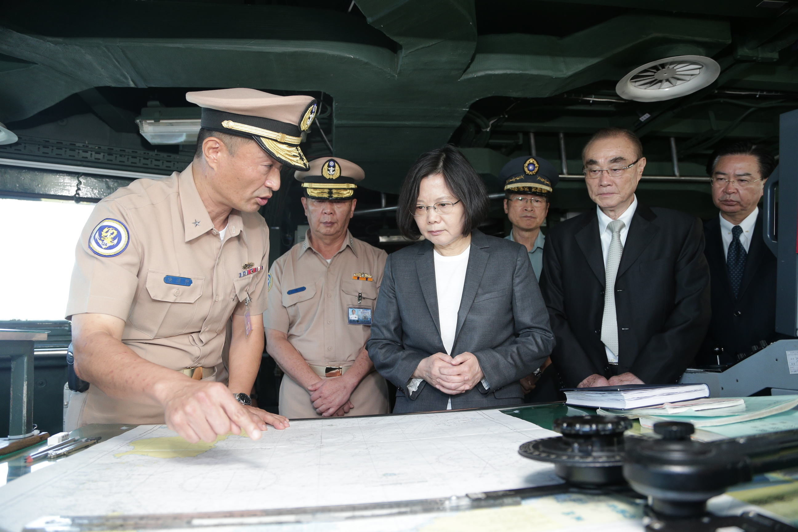 In this image taken and made available by the Taiwan Presidential Office, Taiwan's President Tsai Ing-wen, center right, reviews nautical charts aboard a Taiwan Navy ship before it sets out to patrol in the South China Sea from the naval base in the ...