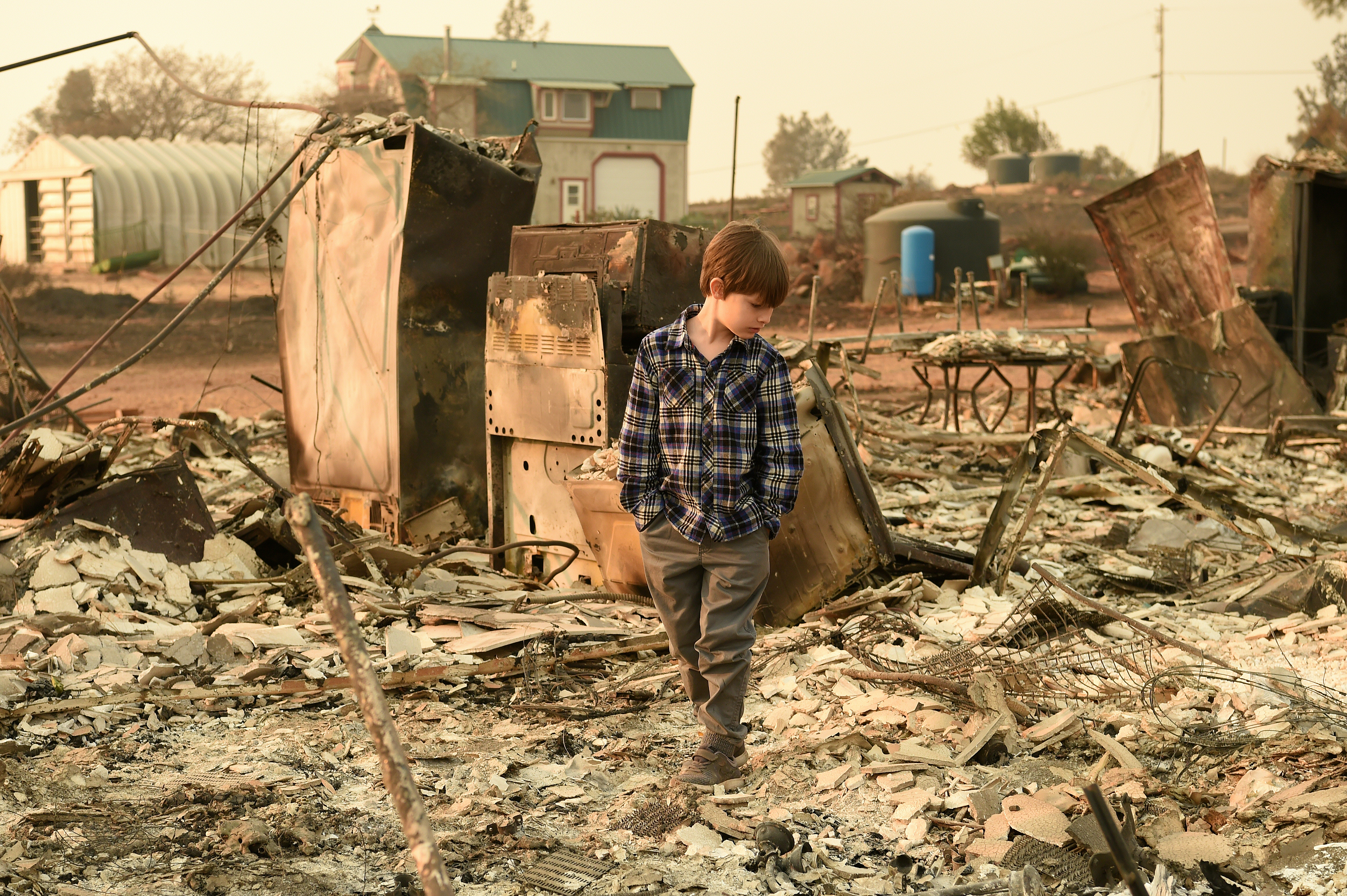 Jacob Saylors, 11, walks through the burned remains of his home in Paradise, California on November 18, 2018. The family lost a home in the same spot to a fire 10 years prior.