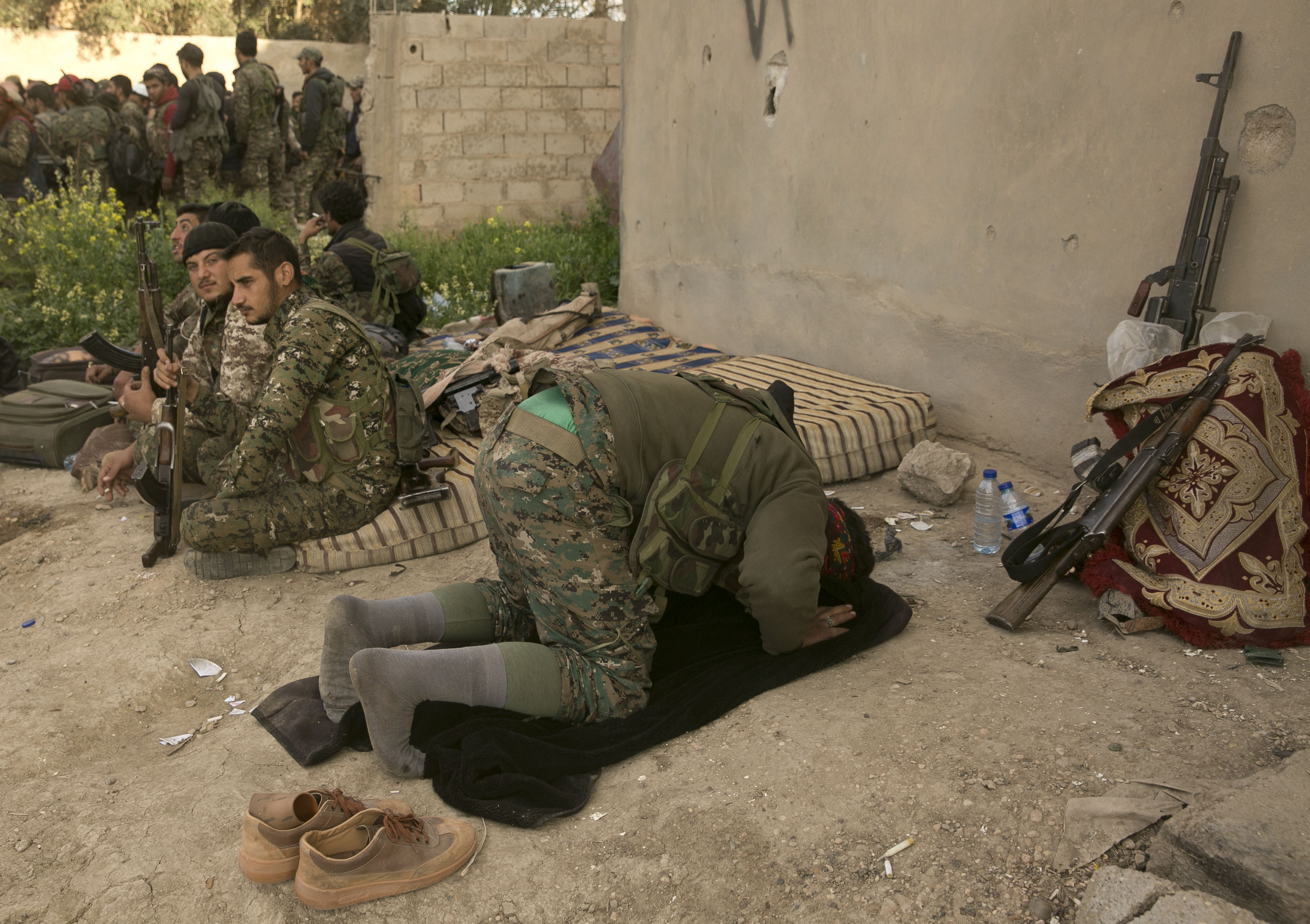 A U.S.-backed Syrian Democratic Forces fighter prays after returning from the front line in their fight against Islamic State militants in Baghuz, Syria, March 19, 2019.