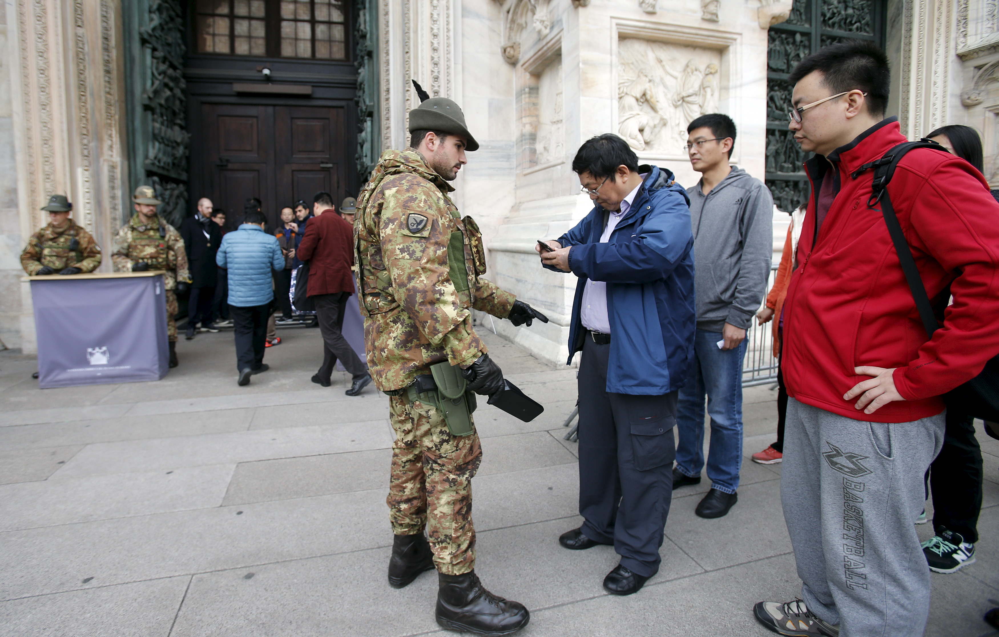 An Alpini Regiment of the Italian Army checks visitors outside the Milan's cathedral, northern Italy, Nov. 20, 2015. Italy and Sweden increased security around public buildings after receiving reports that attacks might be planned on their soil.