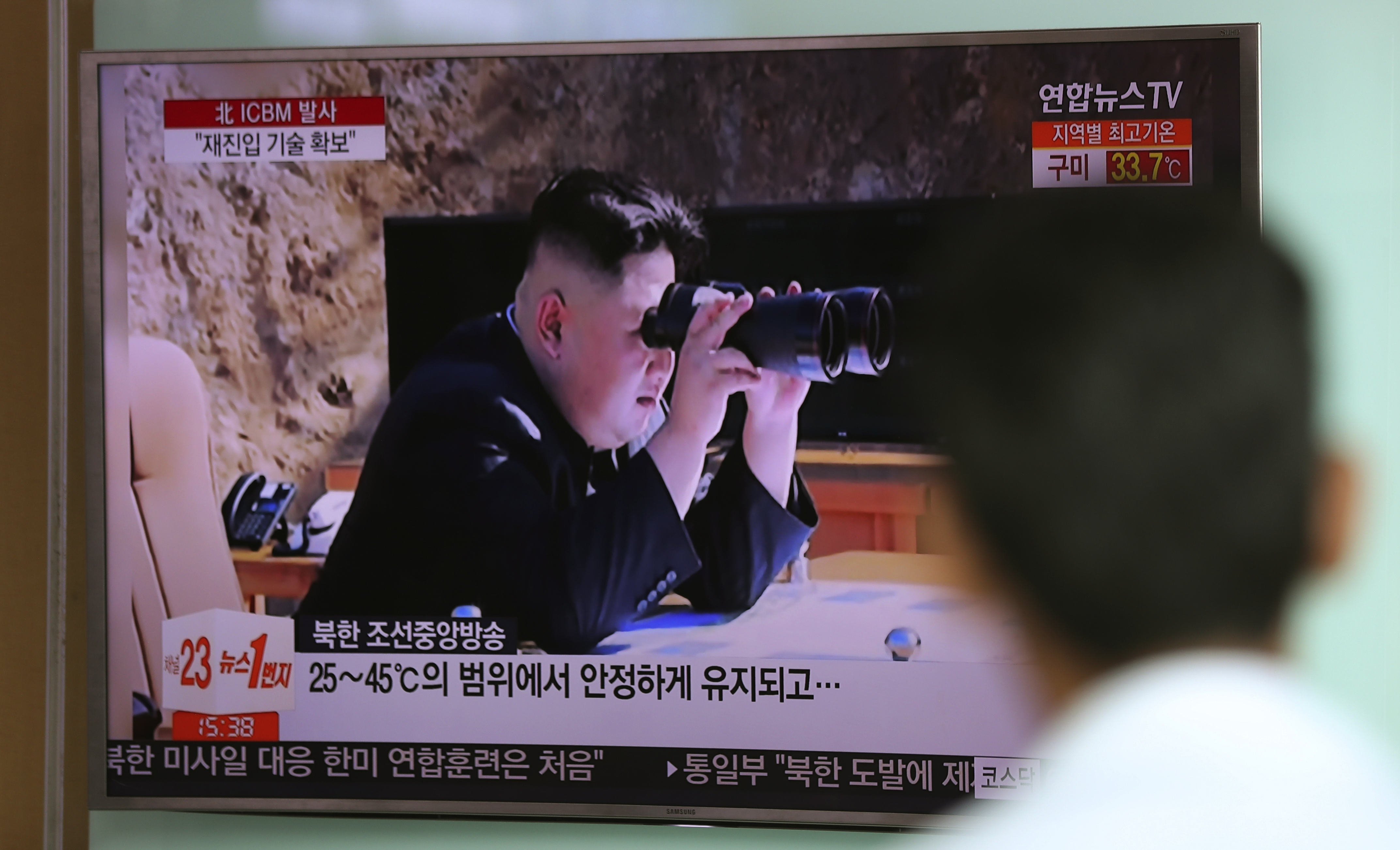 A man watches a TV screen showing a local news program reporting about North Korea's missile firing with an image of North Korean leader Kim Jong Un with a pair of binoculars, at Seoul Train Station in Seoul, South Korea, July 5, 2017.