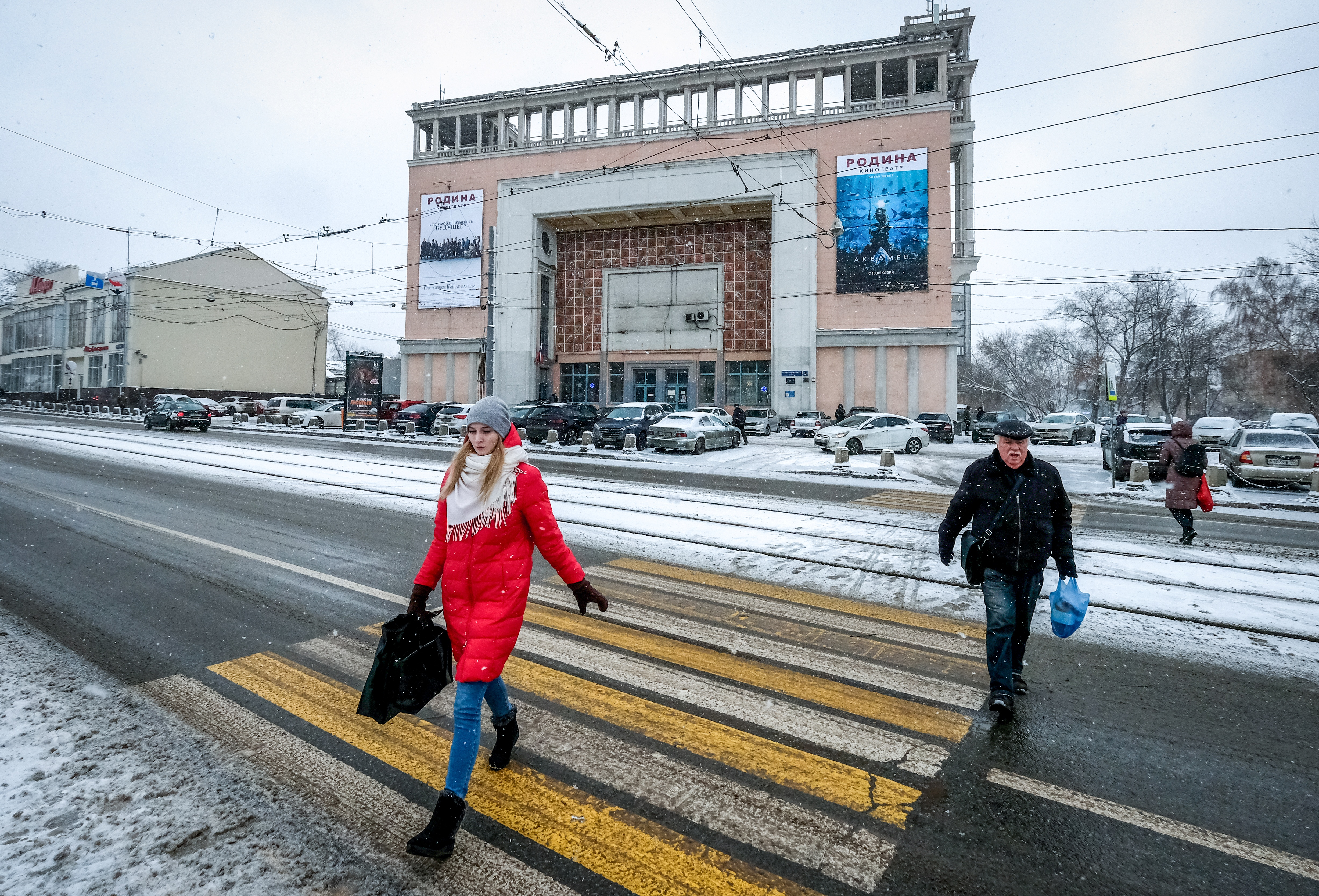 "Pedestrians walk outside the 1938 Rodina (""Motherland"") cinema in northern Moscow, Dec. 13, 2018."