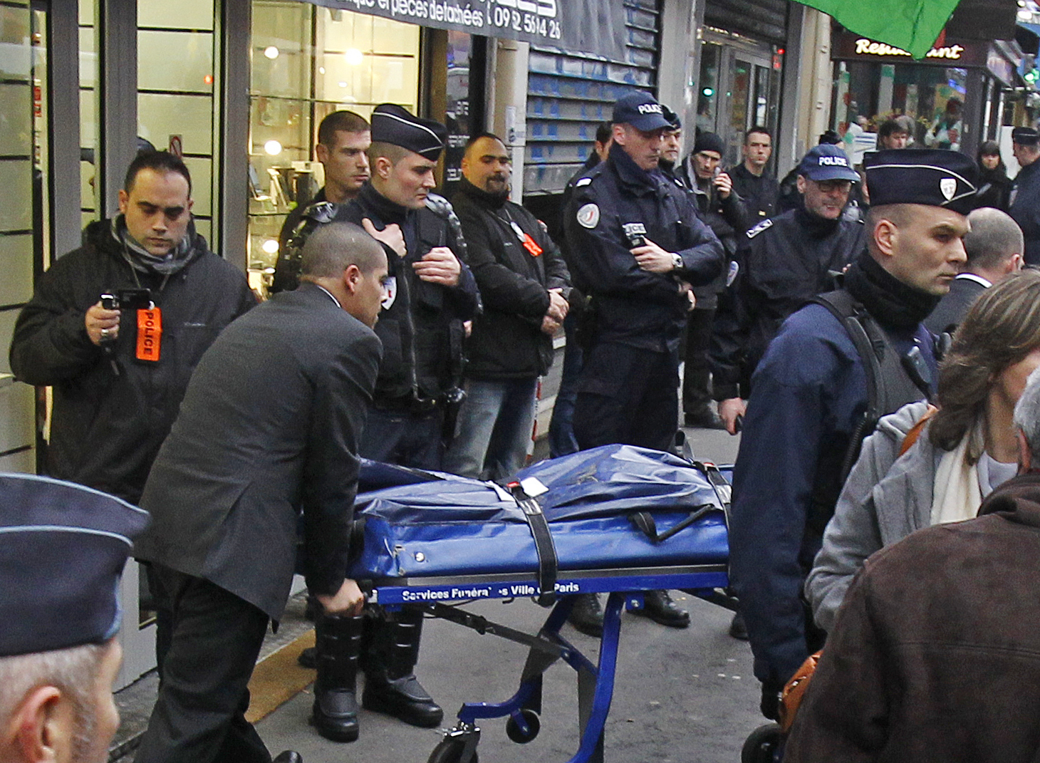 The body of one of the three Kurdish women killed in Paris is taken out of the building where they were shot, January 10, 2012.