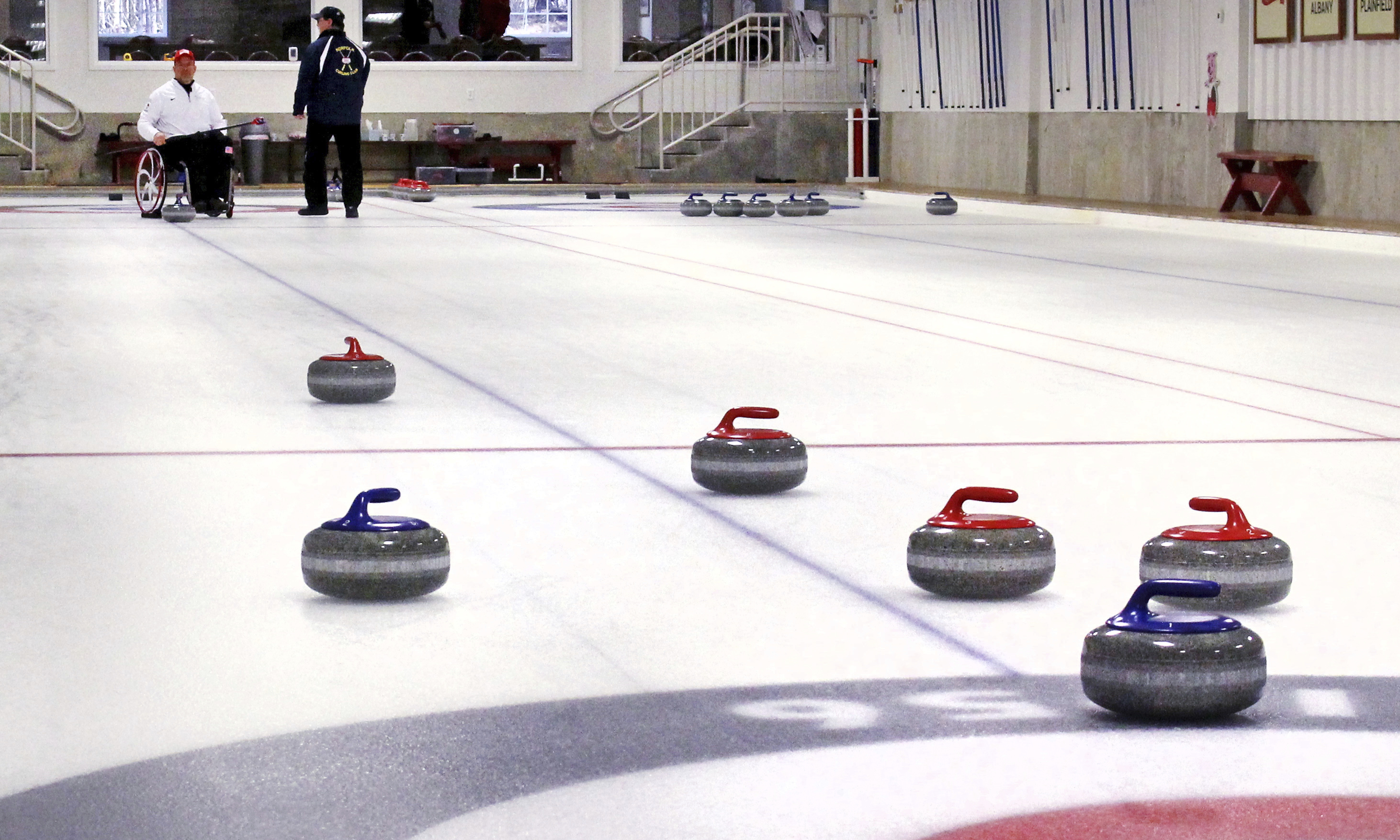 Curling stones rest on the field of play as former Connecticut basketball player Steve Emt practices at the Norfolk Curling Club in Norfolk, Conn., Feb. 21, 2018.