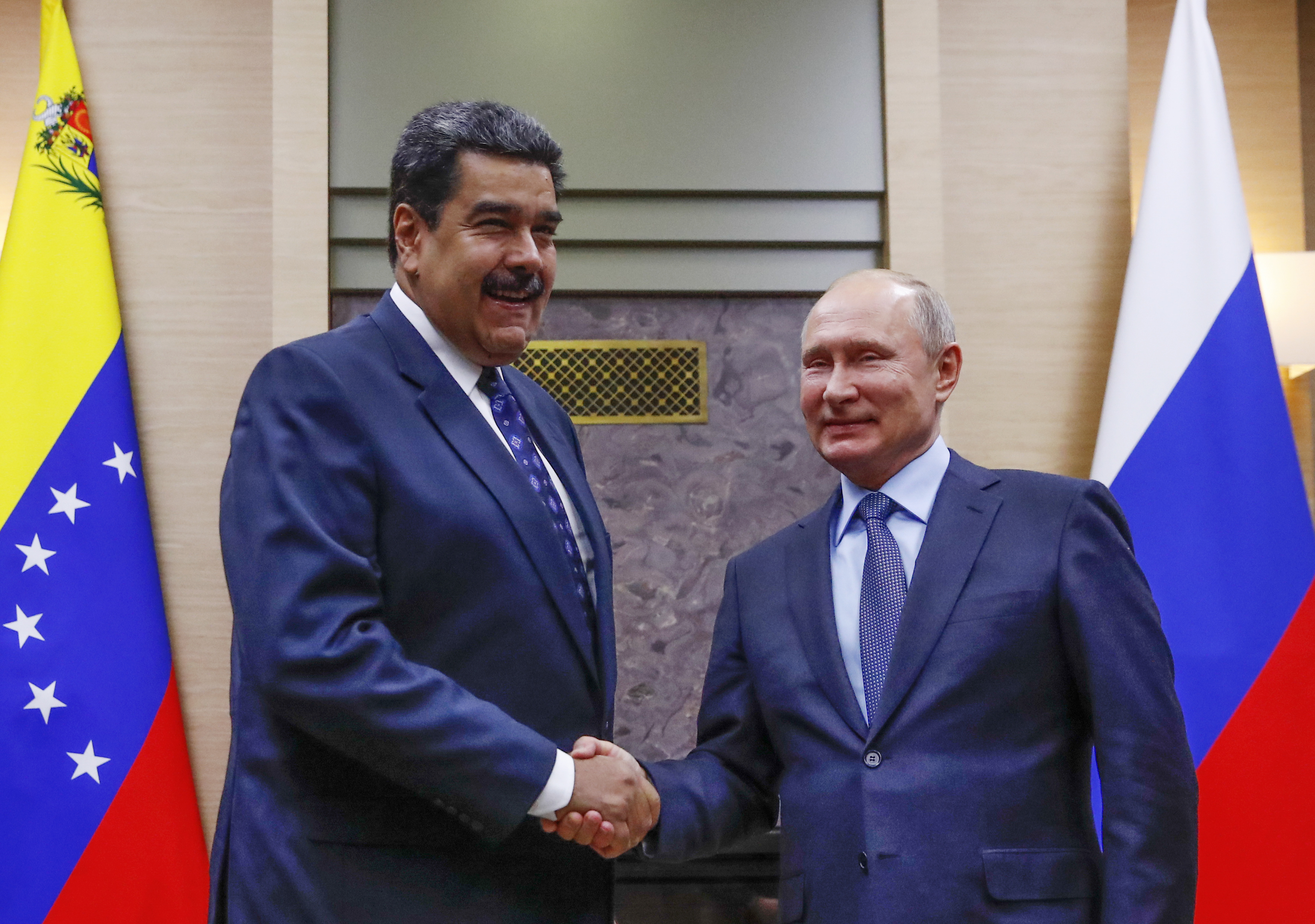 Russian President Vladimir Putin, right, shakes hands with his Venezuelan counterpart Nicolas Maduro during their meeting at the Novo-Ogaryovo residence outside in Moscow, Russia, Dec. 5, 2018.