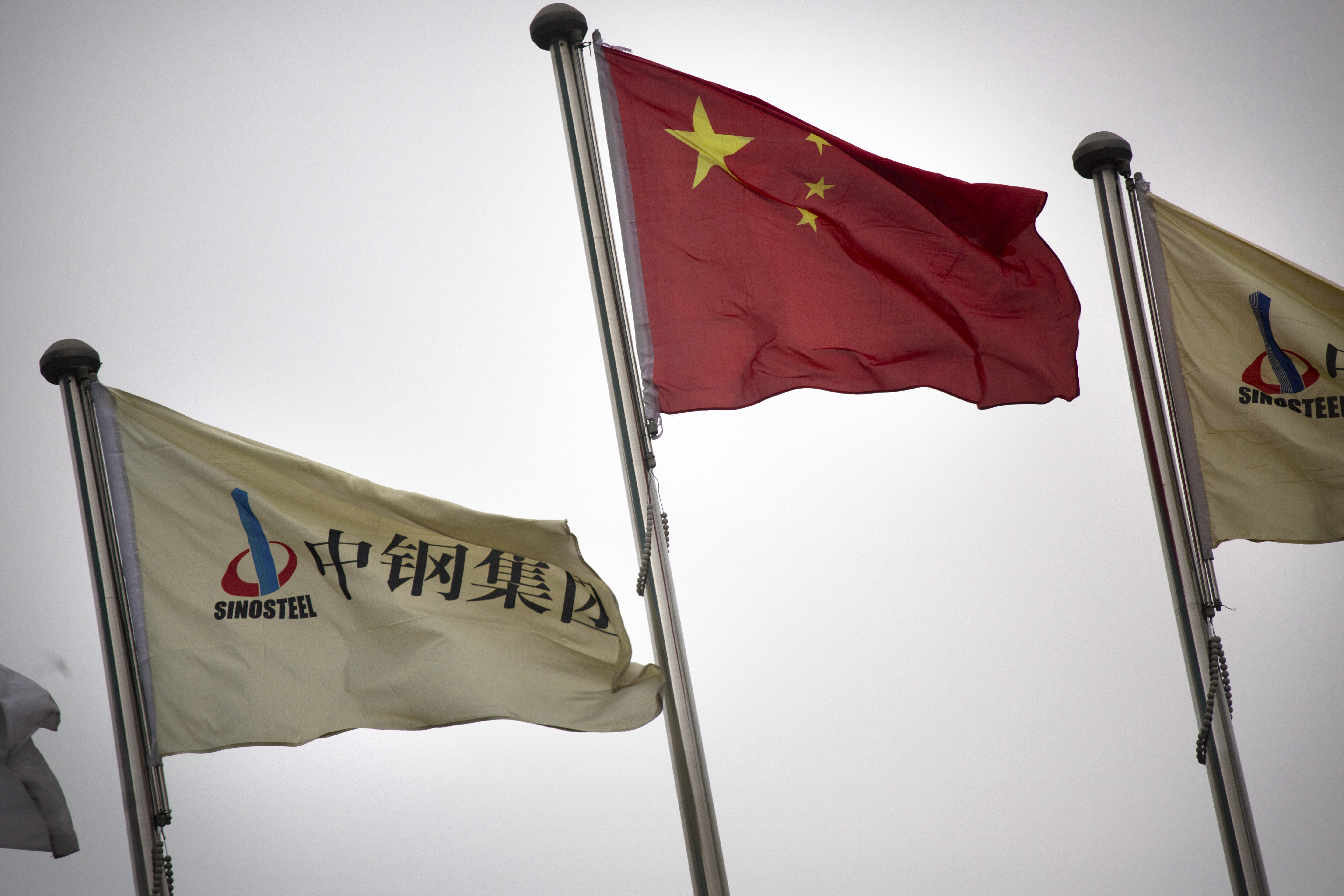 FILE - SinoSteel Corp. and Chinese flags fly outside of the company's headquarters in Beijing, China, Nov. 18, 2015.