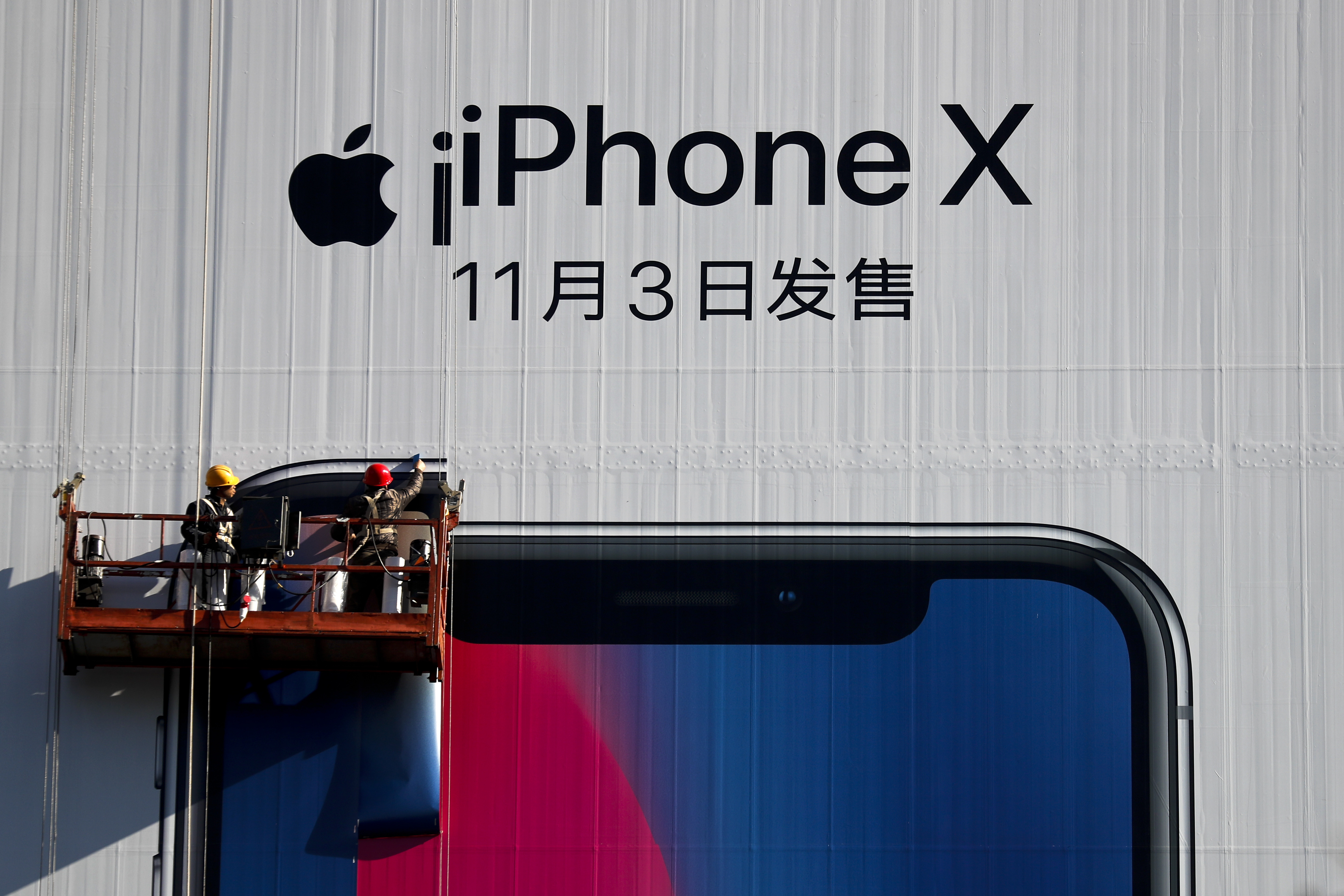 Workers on a suspended platform replace an advertisement poster for the new iPhone X on a building in Beijing, Oct. 30, 2017.