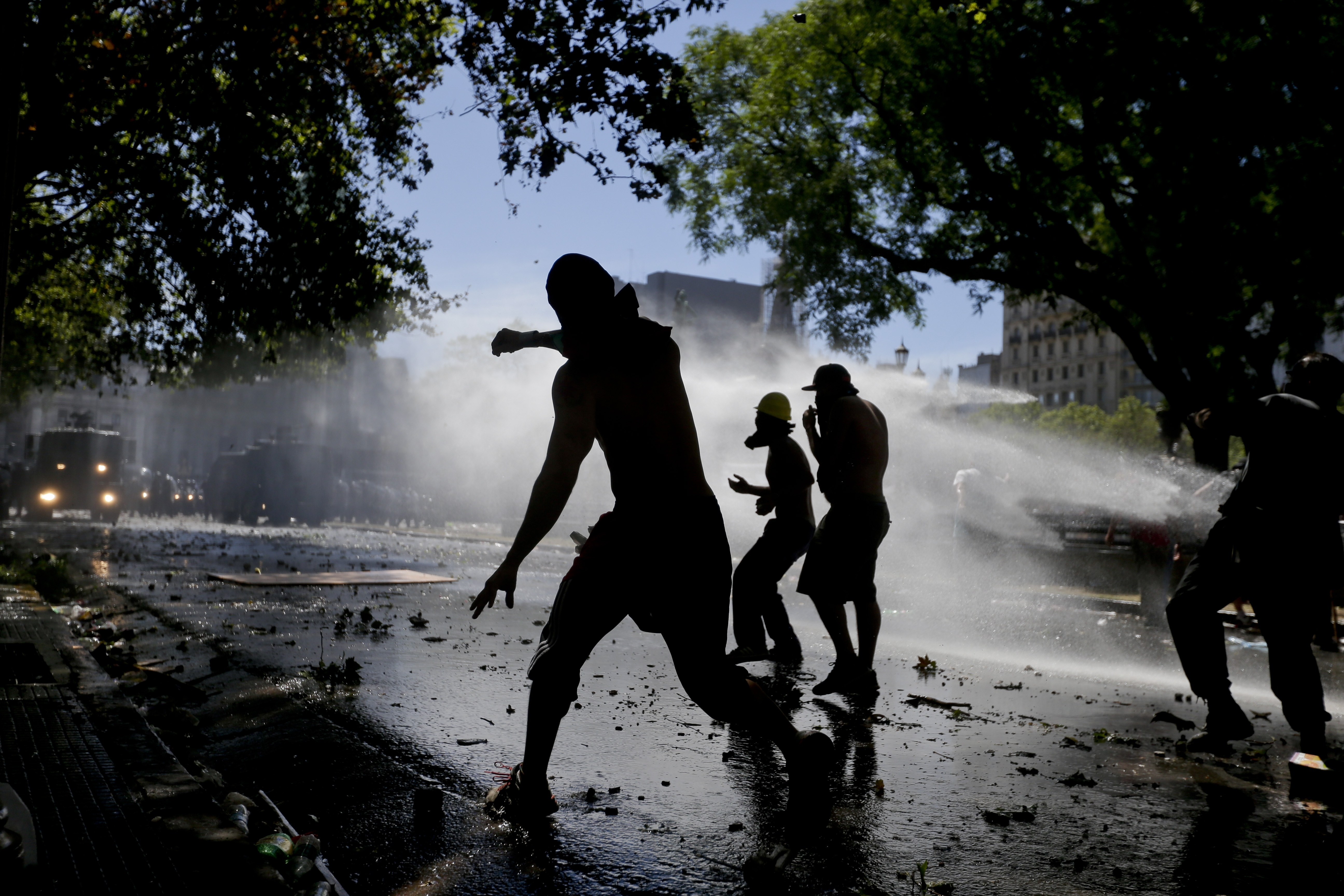 Protesters throwing stones at police are sprayed by water cannons during a general strike against a pension reform measure, outside Congress in Buenos Aires, Argentina, Dec. 18, 2017.