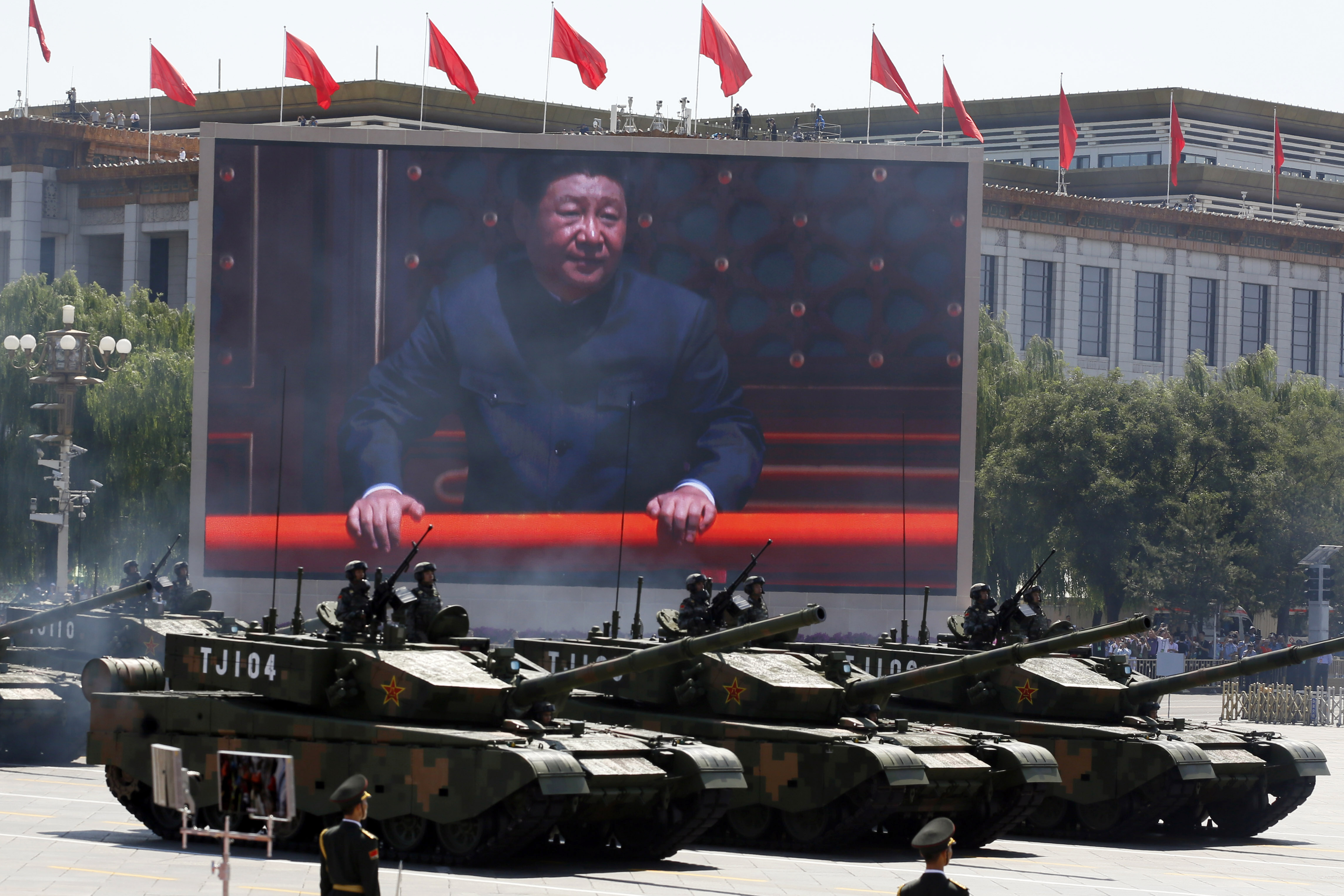 Chinese President Xi Jinping is displayed on a screen as Type 99A2 Chinese battle tanks take part in a parade commemorating the 70th anniversary of Japan's surrender during World War II held in front of Tiananmen Gate in Beijing, Thursday, Sept. 3, 2...