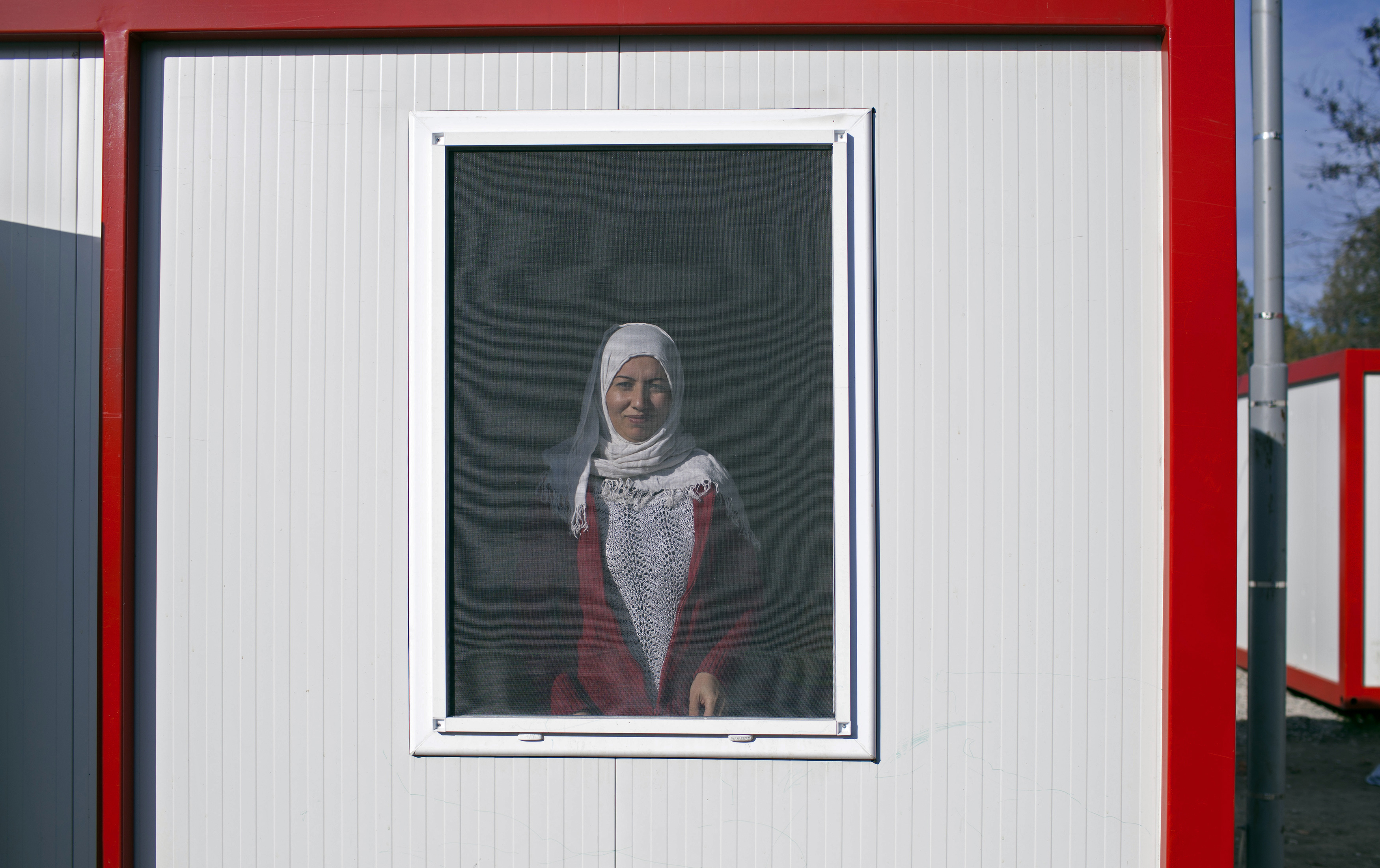 A Syrian woman looks out of the window of a container home at the refugee camp in Harmanli, 280km (174 miles) east of Sofia December 9, 2013. Bulgaria is currently hosting some 11,000 asylum seekers and refugees, around two-thirds of them Syrians. Fo...