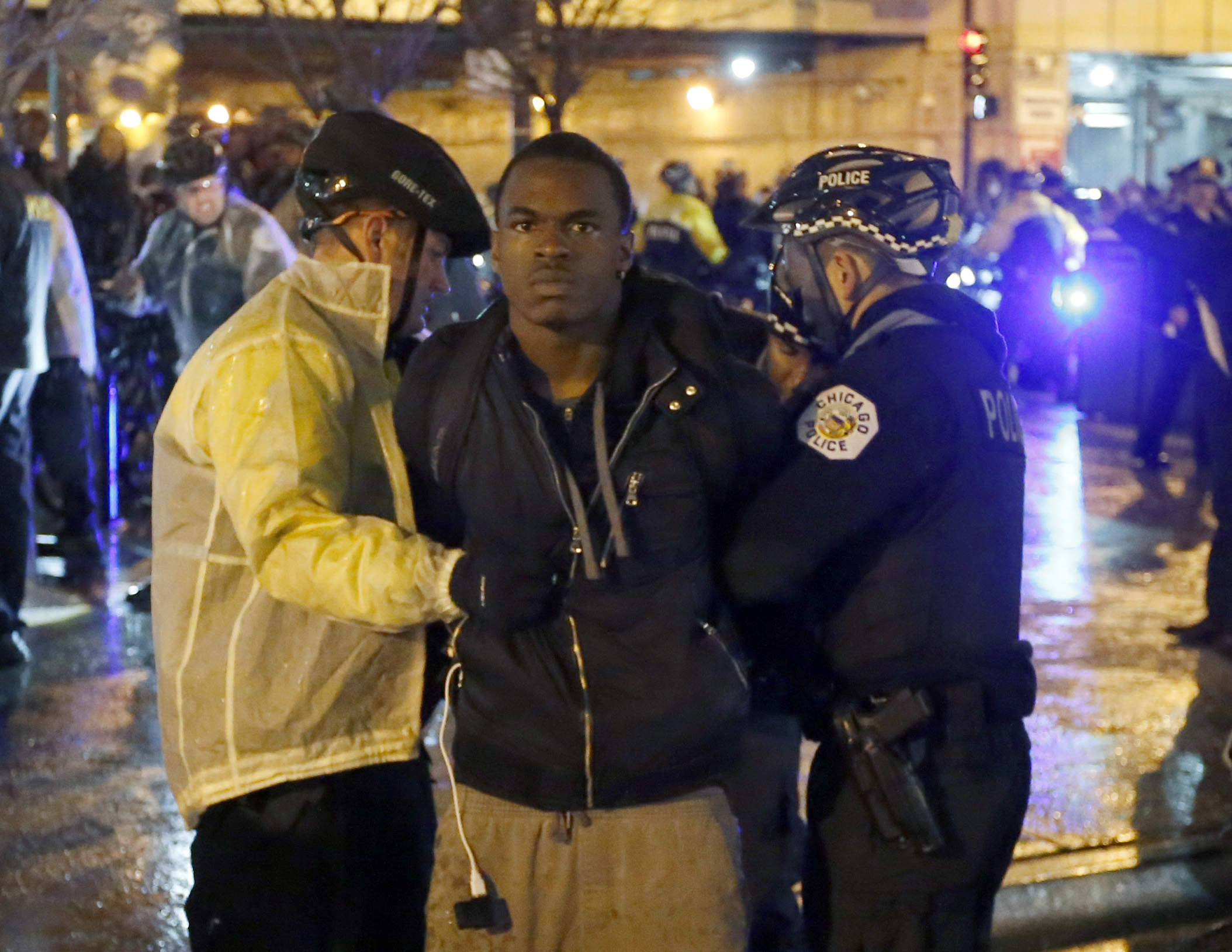 Two Chicago police officers take a man into custody during a protest march, Wednesday, Nov. 25, 2015, in Chicago, the day after murder charges were brought against police officer Jason Van Dyke in the killing of 17-year-old Laquan McDonald.